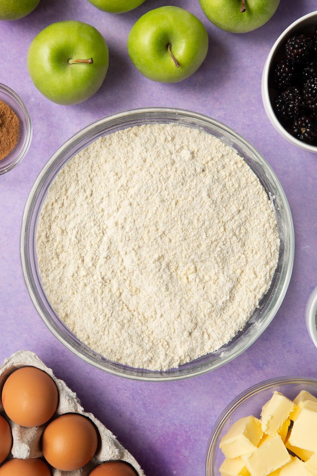 Flour, icing sugar and butter combined to a crumb in a glass mixing bowl. Ingredients to make apple and blackberry pie surround the bowl.