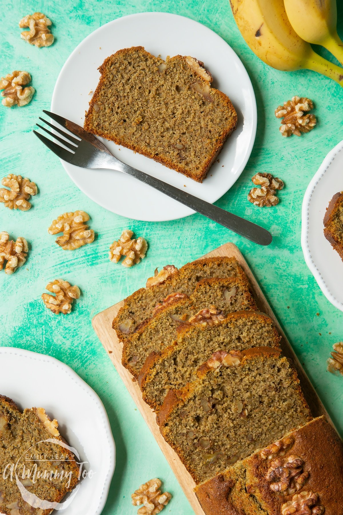 Sliced Matcha banana cake with two servings on white decorative plates.