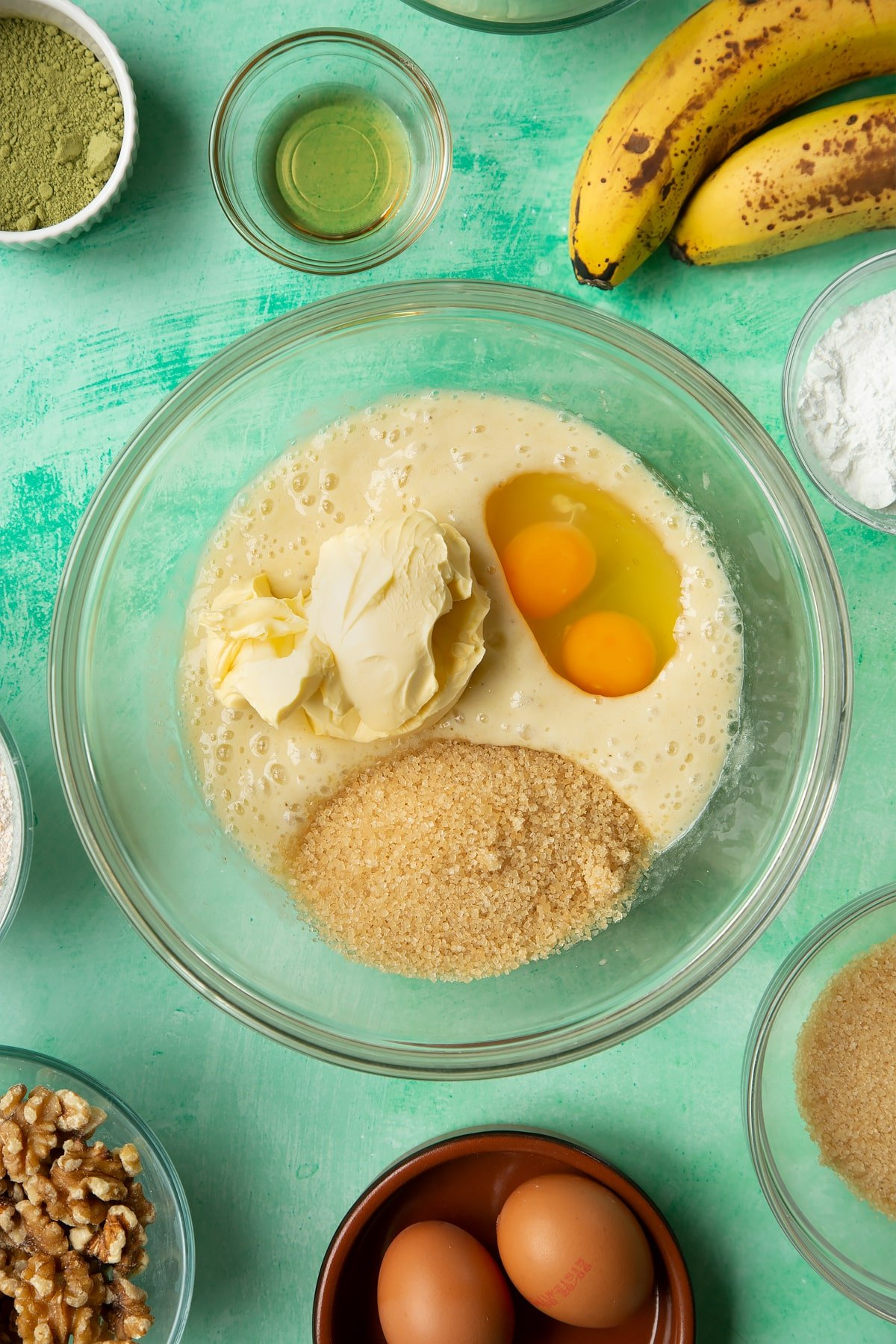 Overhead shot of vanilla, margarine, sugar and eggs in a large clear bowl