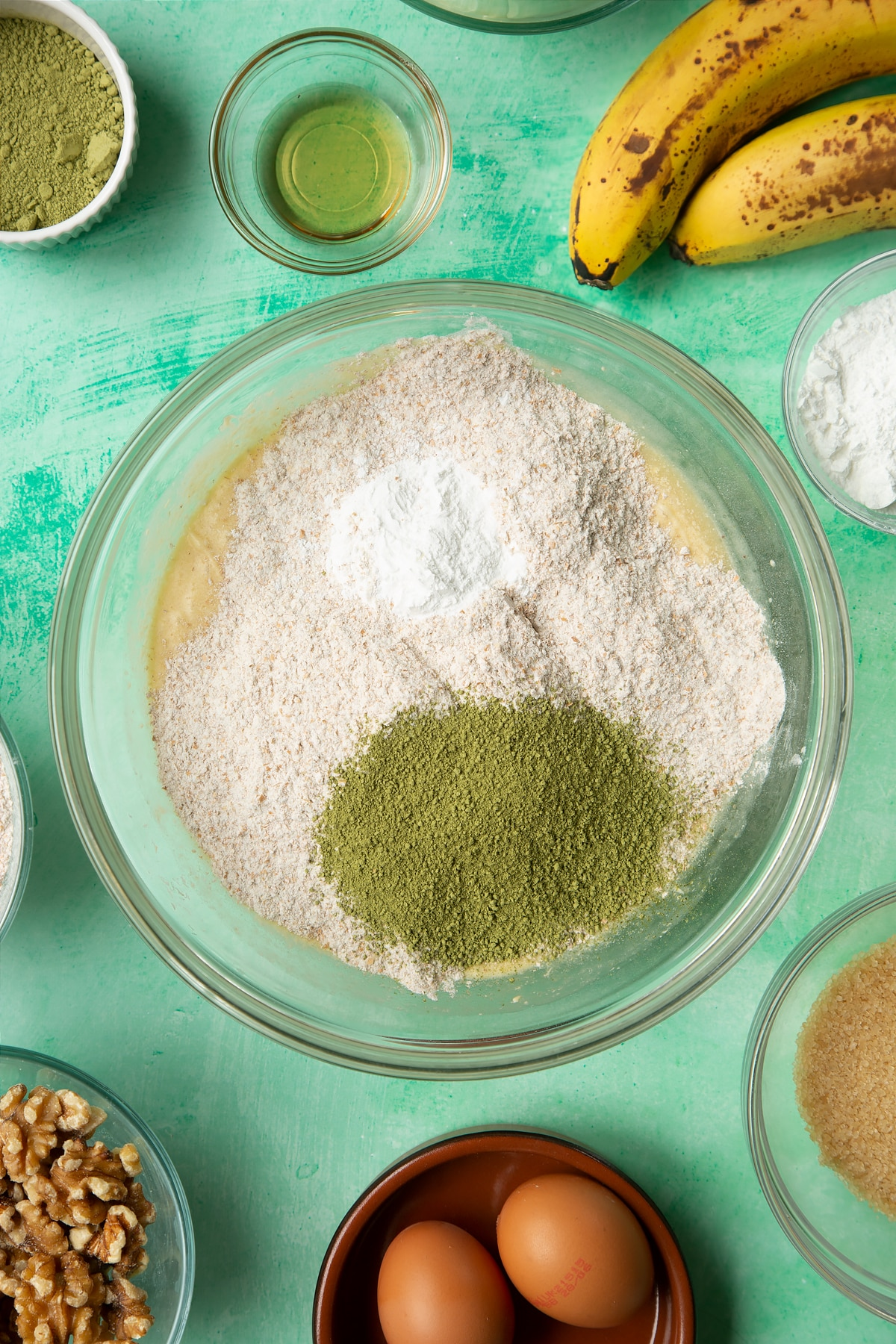 Overhead shot of flour, matcha tea powder and baking powder in a large bowl
