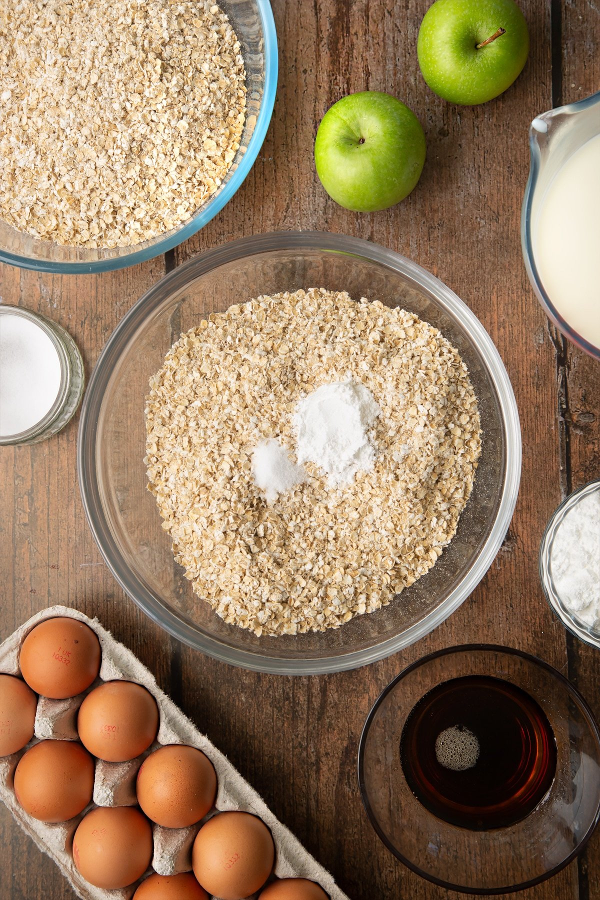 Oats, baking powder and salt in a glass mixing bowl. Ingredients to make porridge squares surround the bowl.