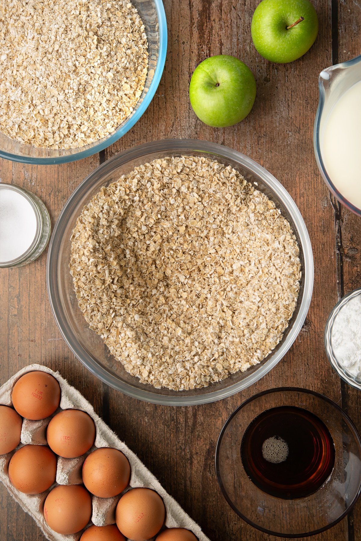Oats, baking powder and salt whisked together in a glass mixing bowl. Ingredients to make porridge squares surround the bowl.