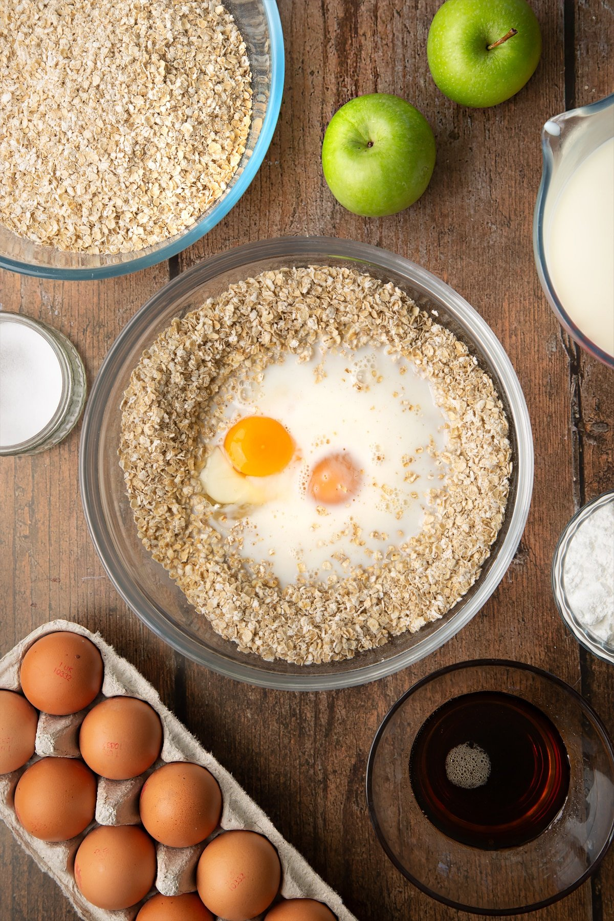 Oats, baking powder, salt, milk, eggs and maple syrup in a glass mixing bowl. Ingredients to make porridge squares surround the bowl.