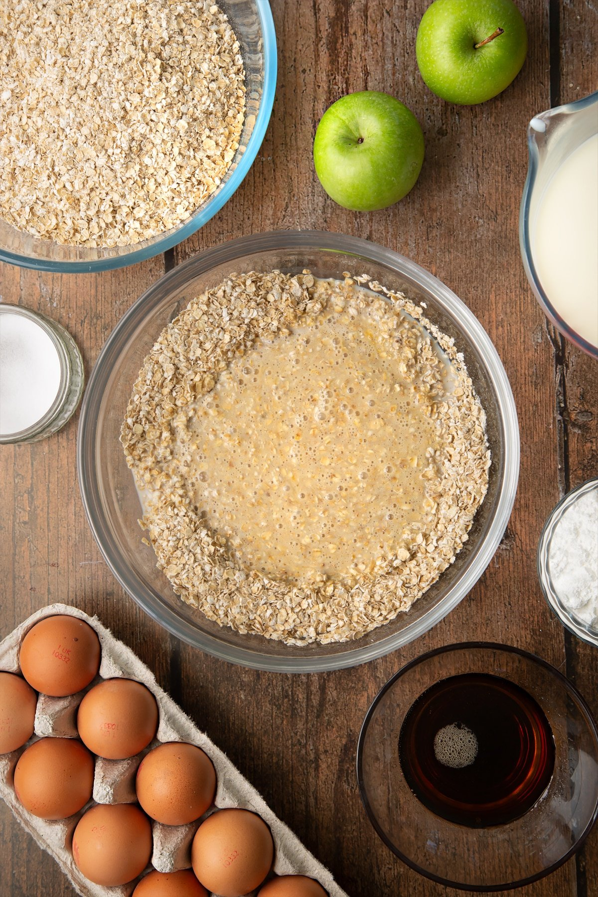 Oats, baking powder, salt, milk, eggs and maple syrup, semi mixed in a glass mixing bowl. Ingredients to make porridge squares surround the bowl.