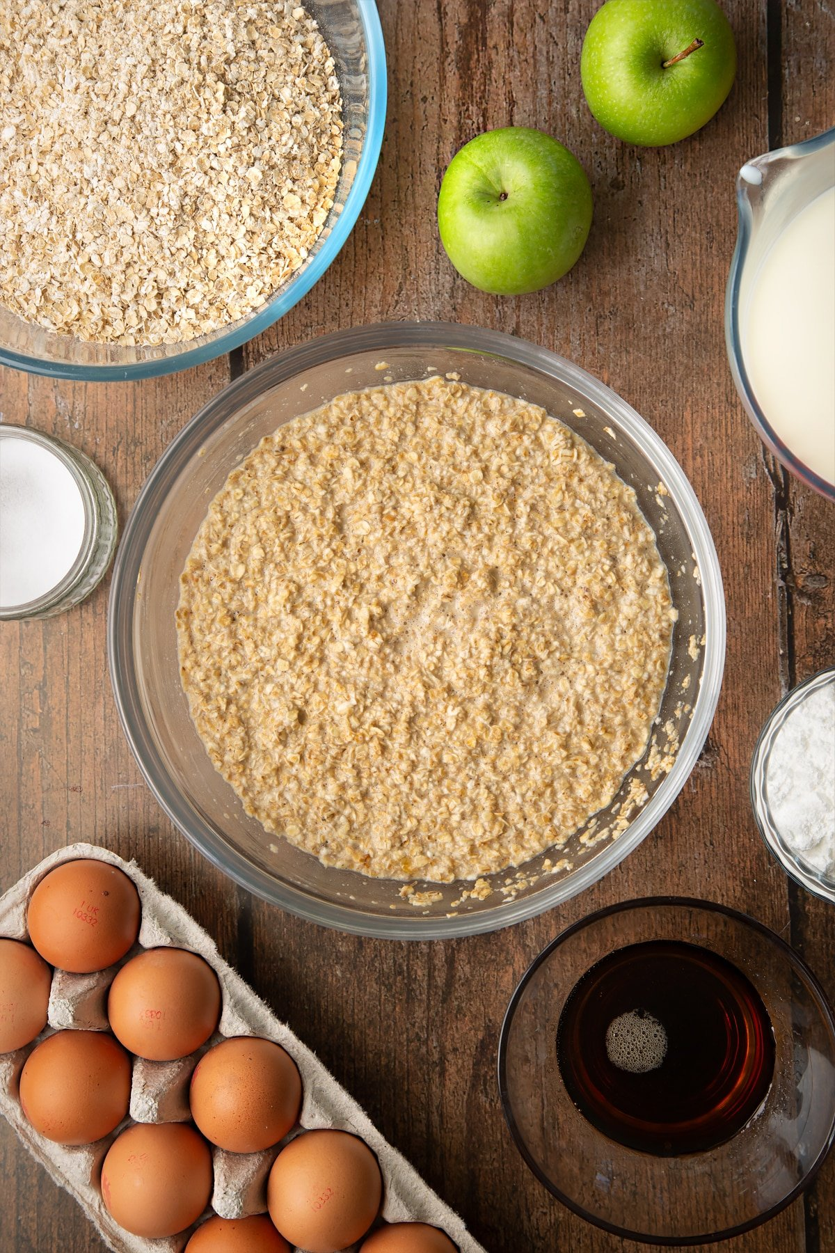 Oats, baking powder, salt, milk, eggs and maple syrup, mixed in a glass mixing bowl. Ingredients to make porridge squares surround the bowl.