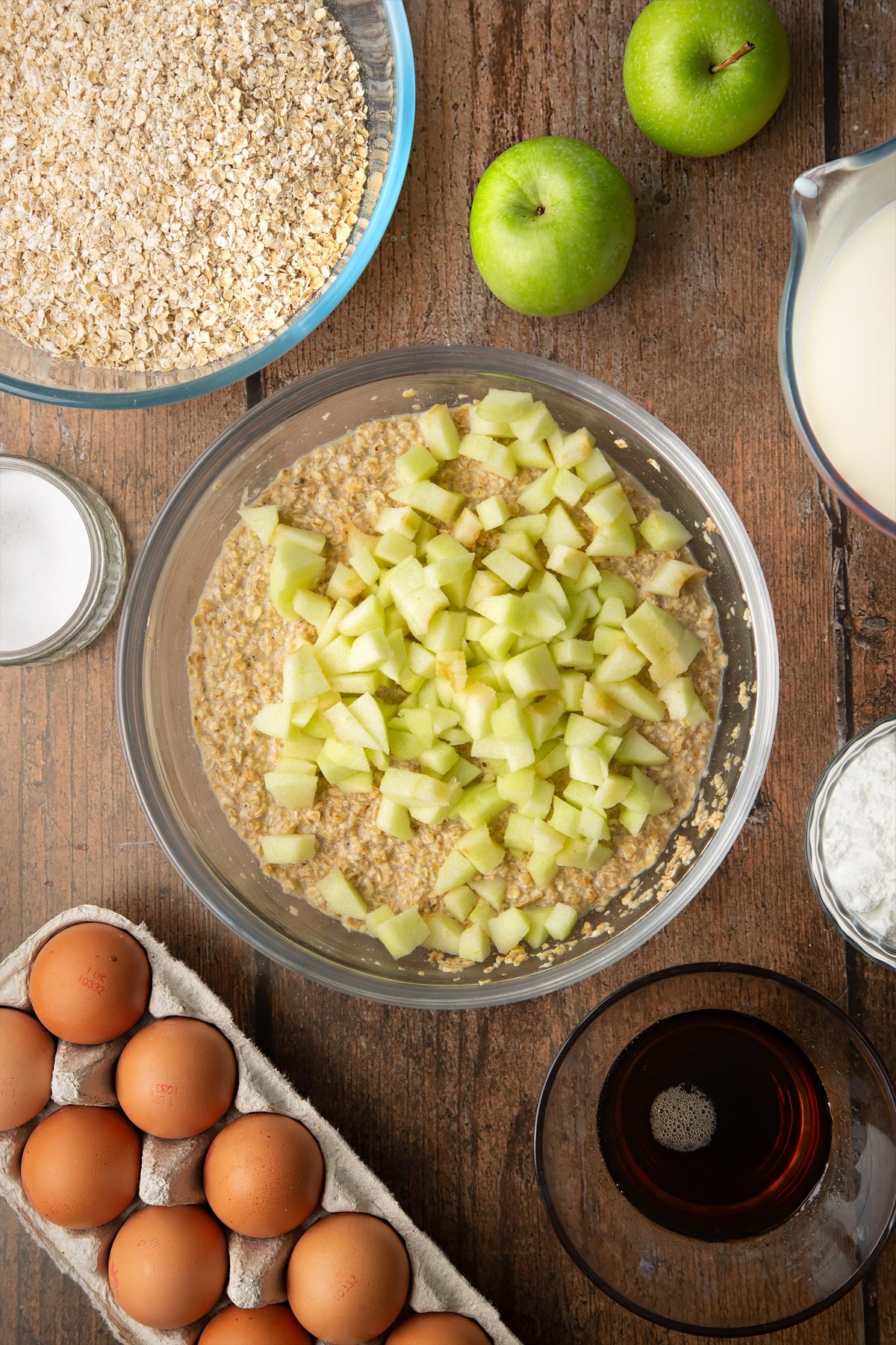 Oats, baking powder, salt, milk, eggs and maple syrup, mixed in a glass mixing bowl with apple pieces on top. Ingredients to make porridge squares surround the bowl.