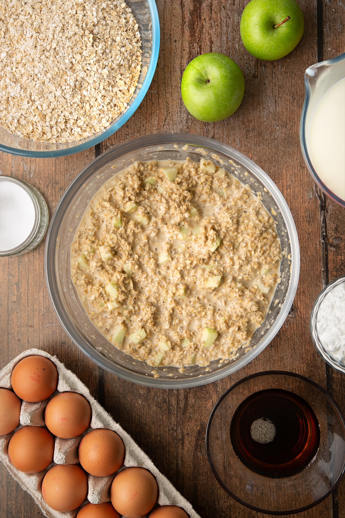 Oats, baking powder, salt, milk, eggs, maple syrup and apple mixed in a glass mixing bowl. Ingredients to make porridge squares surround the bowl.