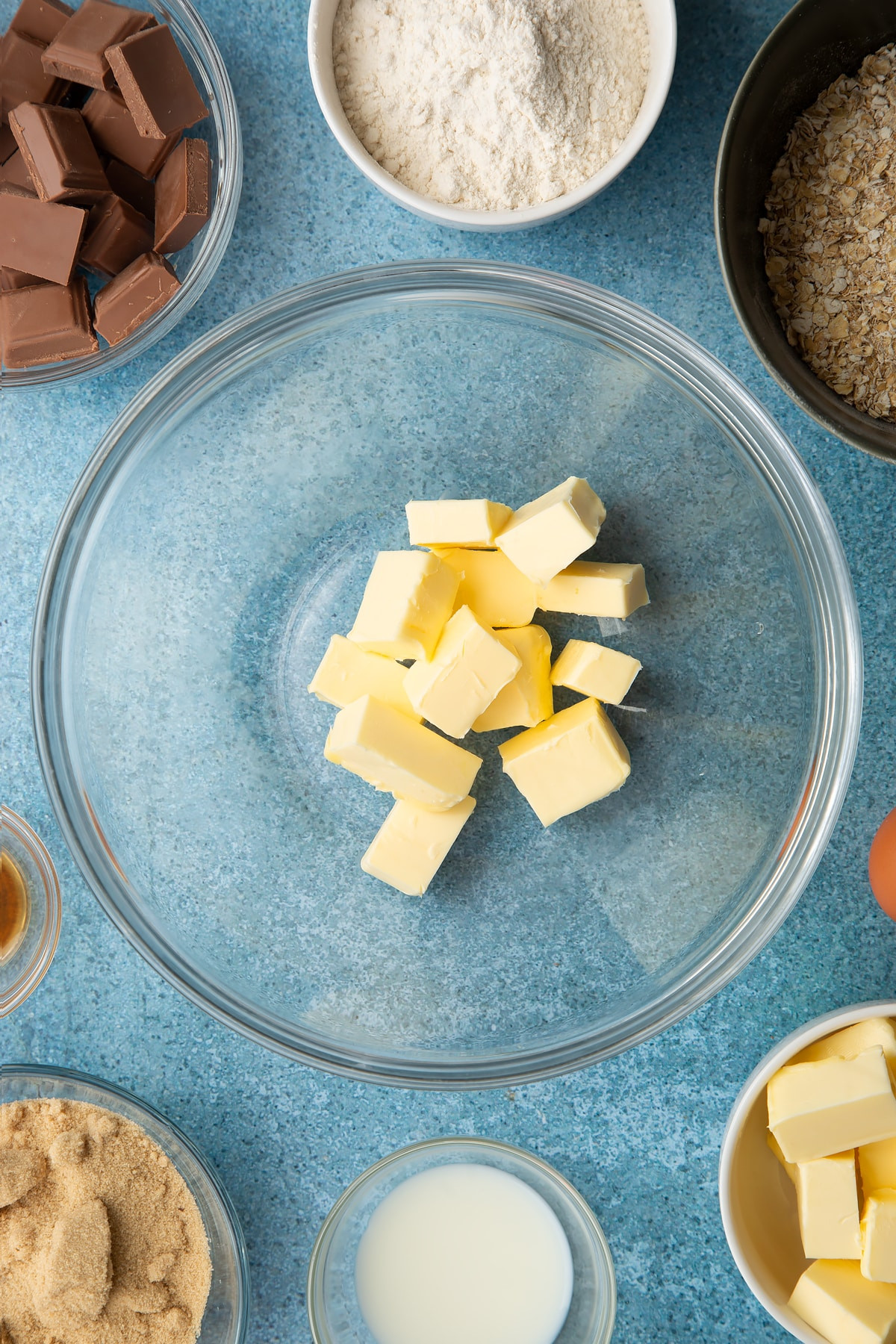 Cubed butter in a glass mixing bowl. Ingredients to make cookie monster cookies surround the bowl.
