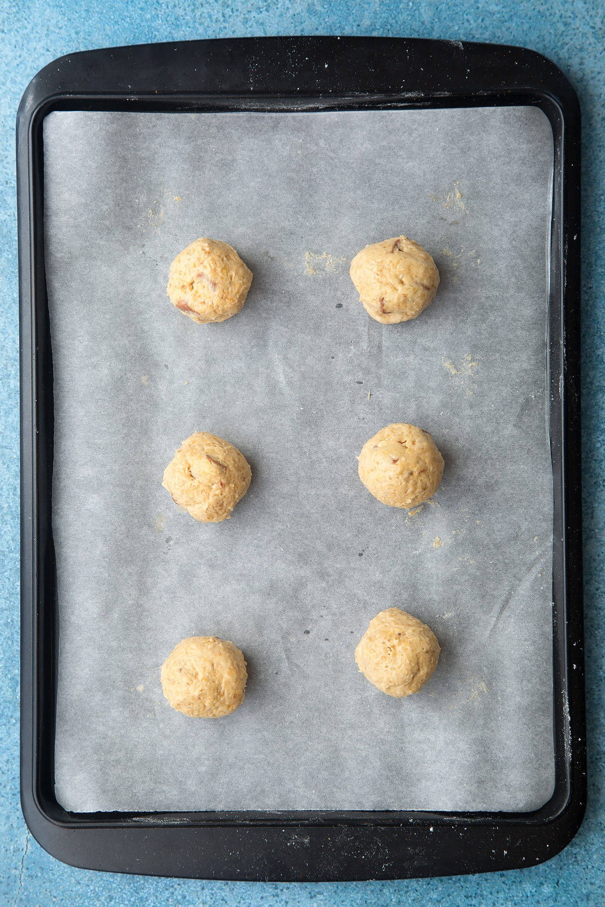 Balls of cookie monster cookie dough on baking tray lined with baking paper.