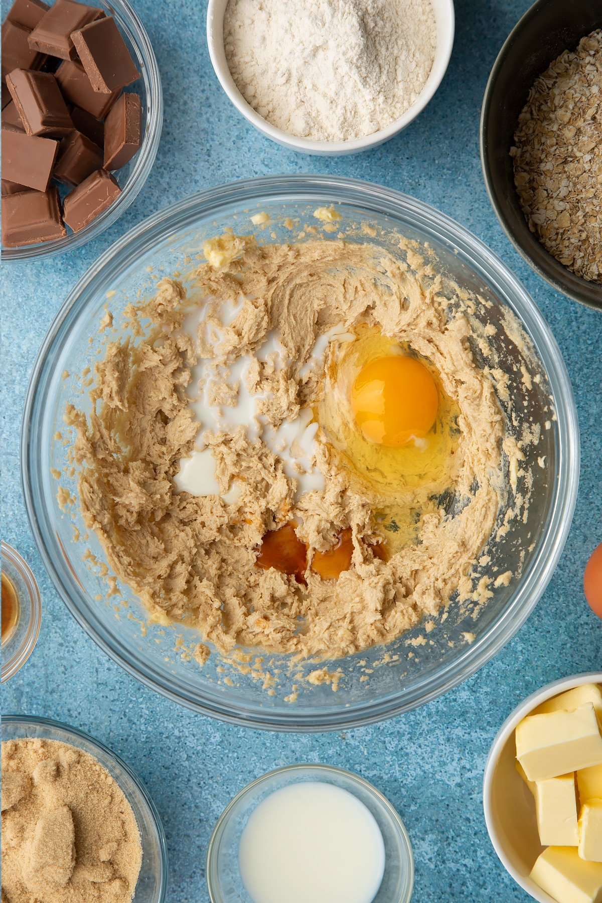 Butter and sugar beaten together in a glass mixing bowl with eggs, vanilla and milk on top. Ingredients to make cookie monster cookies surround the bowl.