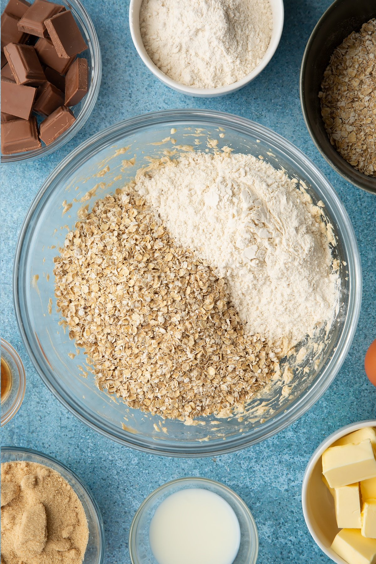Butter, sugar, eggs, vanilla and milk beaten together in a glass mixing bowl with oats and flour on top. Ingredients to make cookie monster cookies surround the bowl.