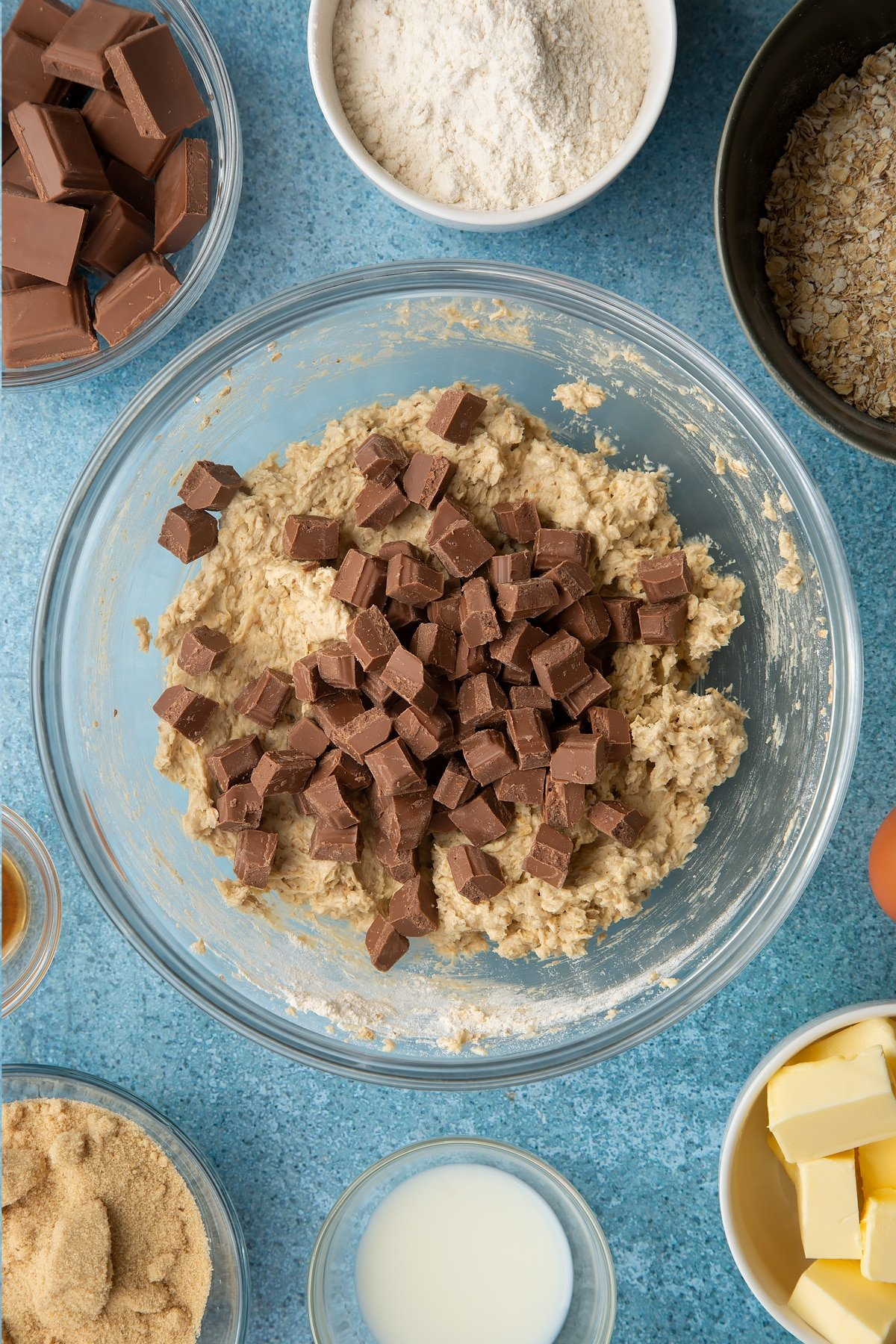 Oatmeal cookie dough in a glass mixing bowl with chocolate chips on top. Ingredients to make cookie monster cookies surround the bowl.