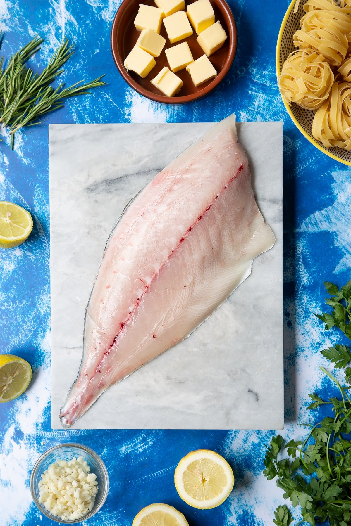 A Dutch Yellowtail fillet on a marble board, skin side down. Hand shown for scale