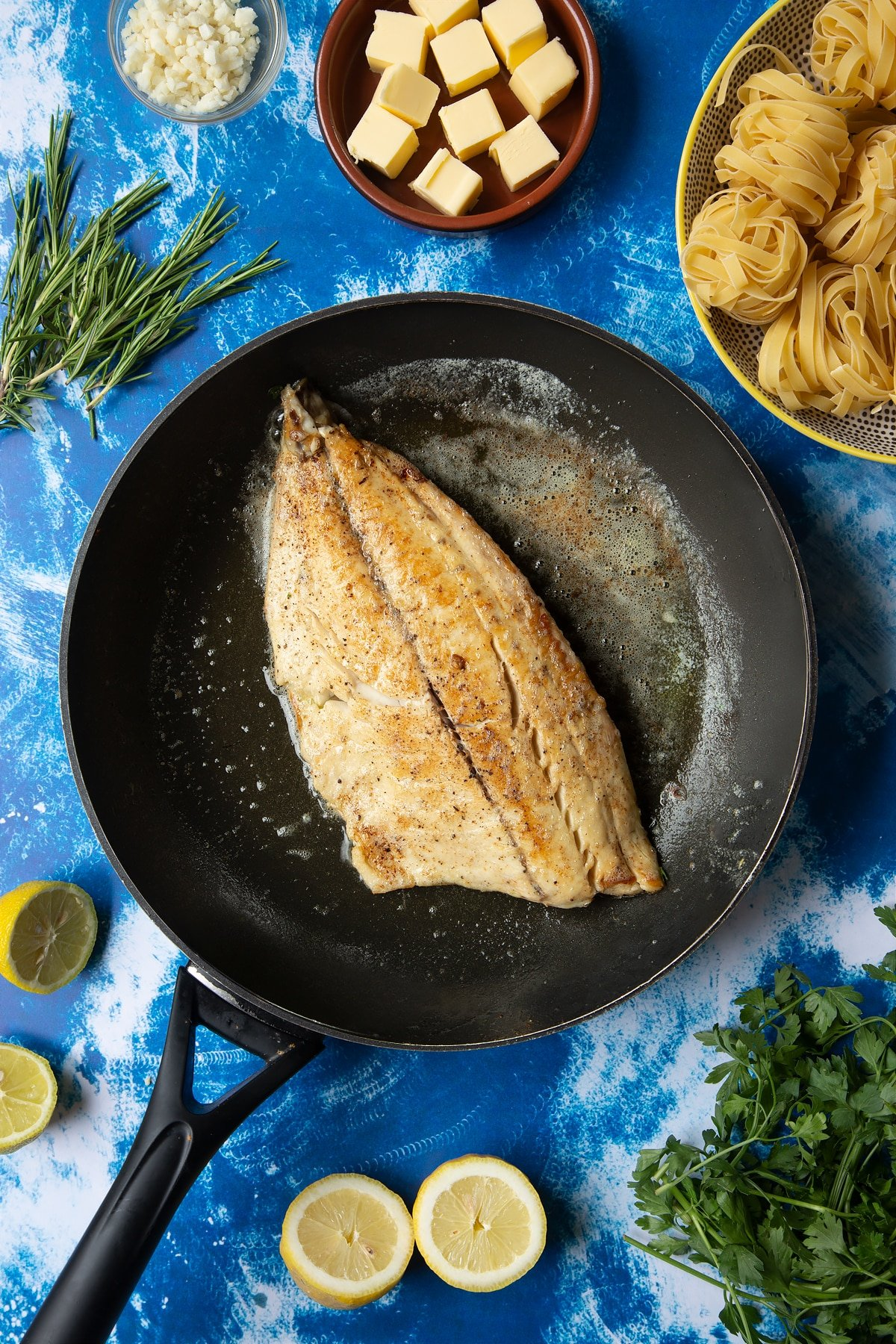 A large frying pan with melted butter and a fish fillet, skin side down. The fillet is cooked and lightly golden. Ingredients to make Dutch Yellowtail tagliatelle surround the pan.