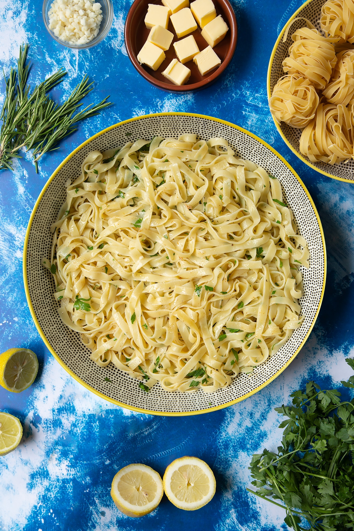 A large bowl with tagliatelle, rosemary and parsley. Ingredients to make Dutch Yellowtail tagliatelle surround the bowl.