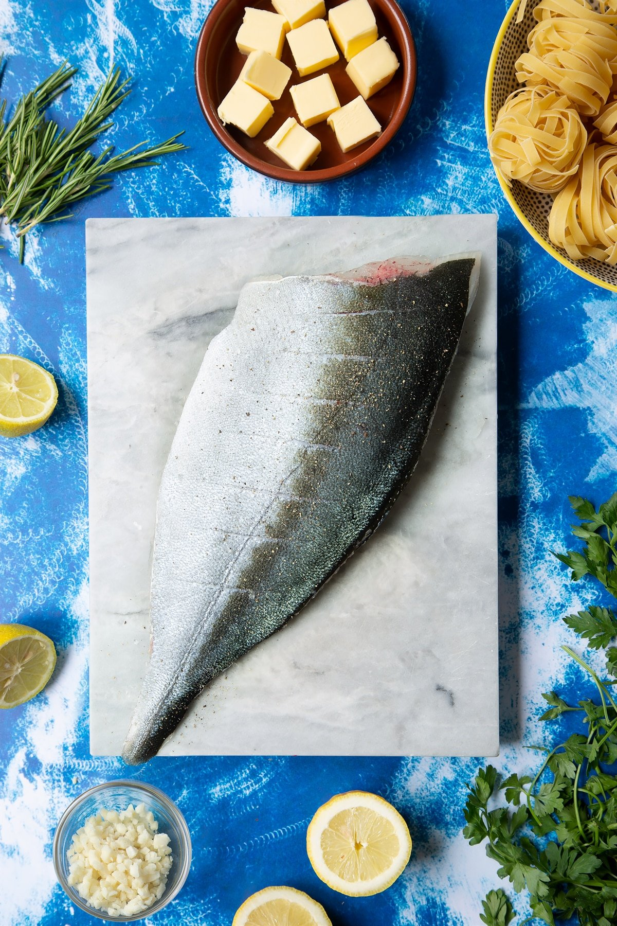 A Dutch Yellowtail fillet on a marble board, skin side up. The fish is seasoned with salt and pepper and the skin in scored.