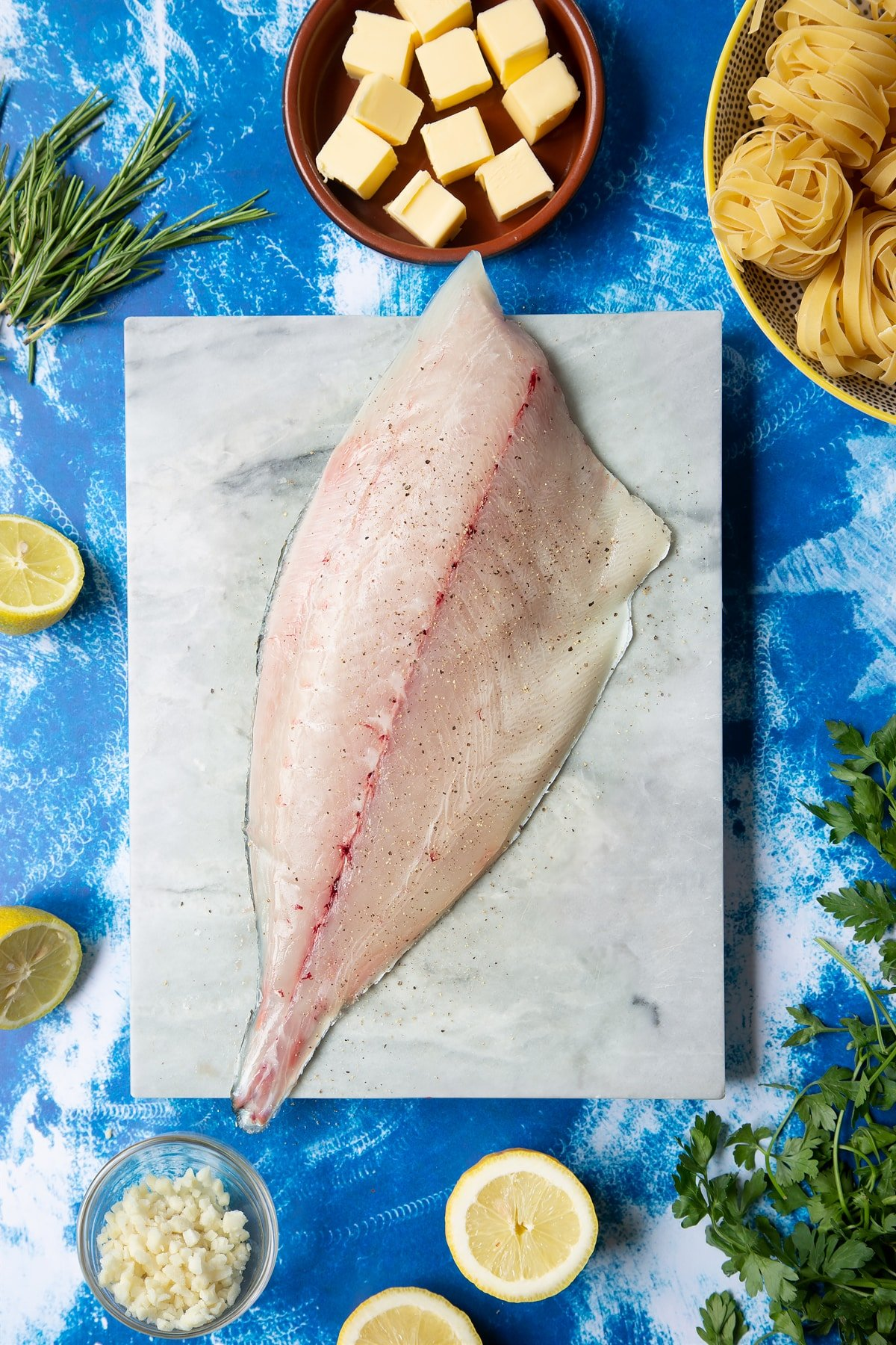 A Dutch Yellowtail fillet on a marble board, skin side down, seasoned with salt and pepper. Hand shown for scale