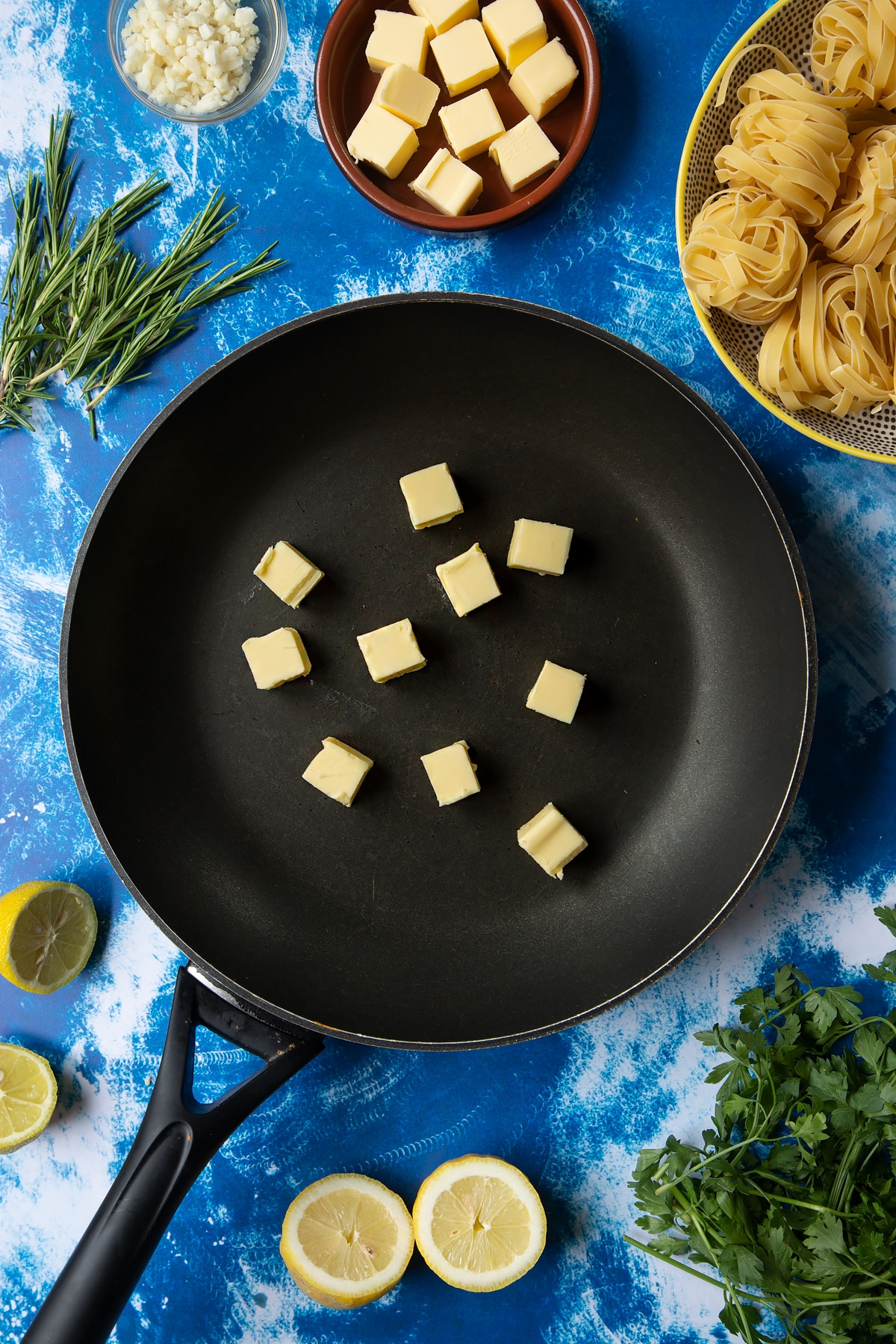 A large frying pan with cubes of butter. Ingredients to make Dutch Yellowtail tagliatelle surround the pan.