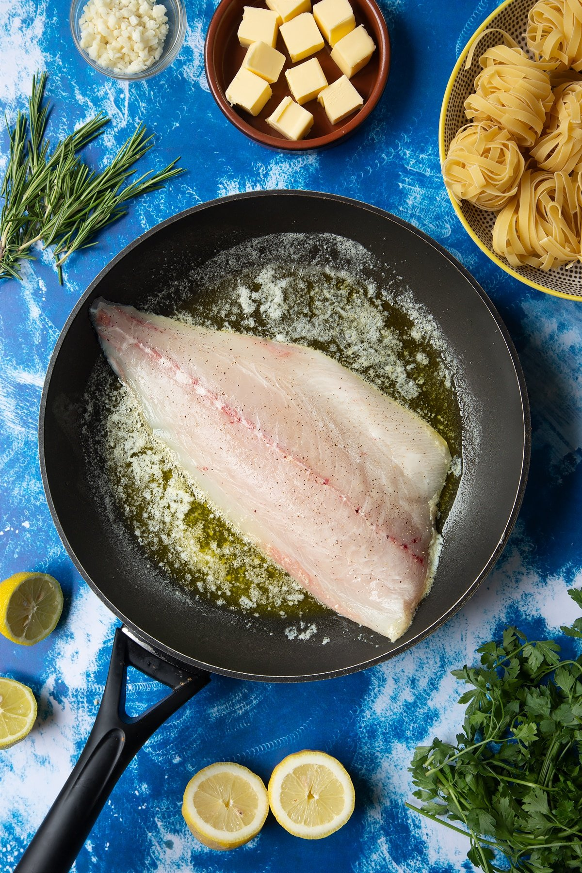 A large frying pan with melted butter and a fish fillet, skin side down. Ingredients to make Dutch Yellowtail tagliatelle surround the pan.