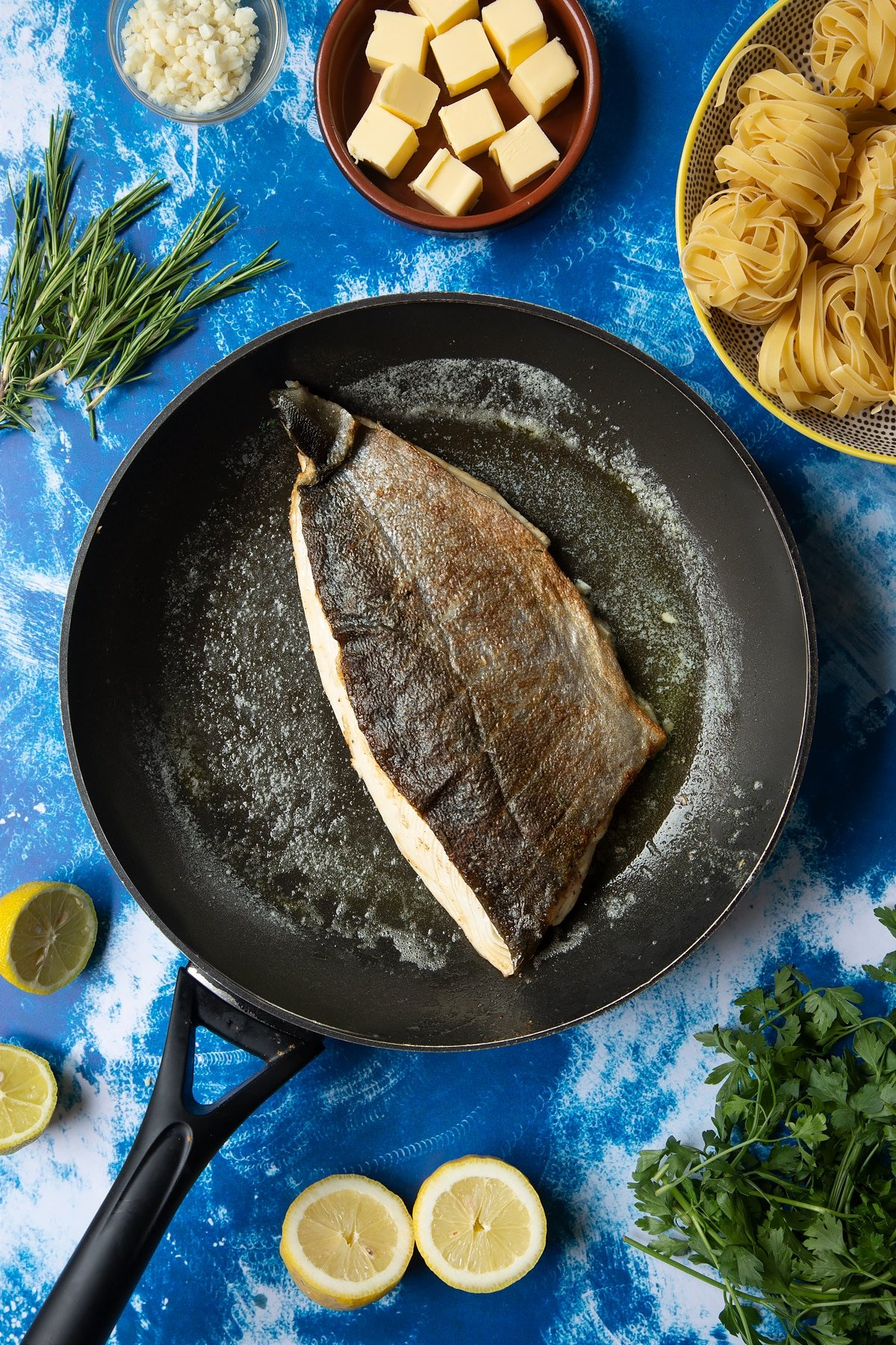 A large frying pan with melted butter and a fish fillet, skin side up. The skin is cooked and crisp. Ingredients to make Dutch Yellowtail tagliatelle surround the pan.