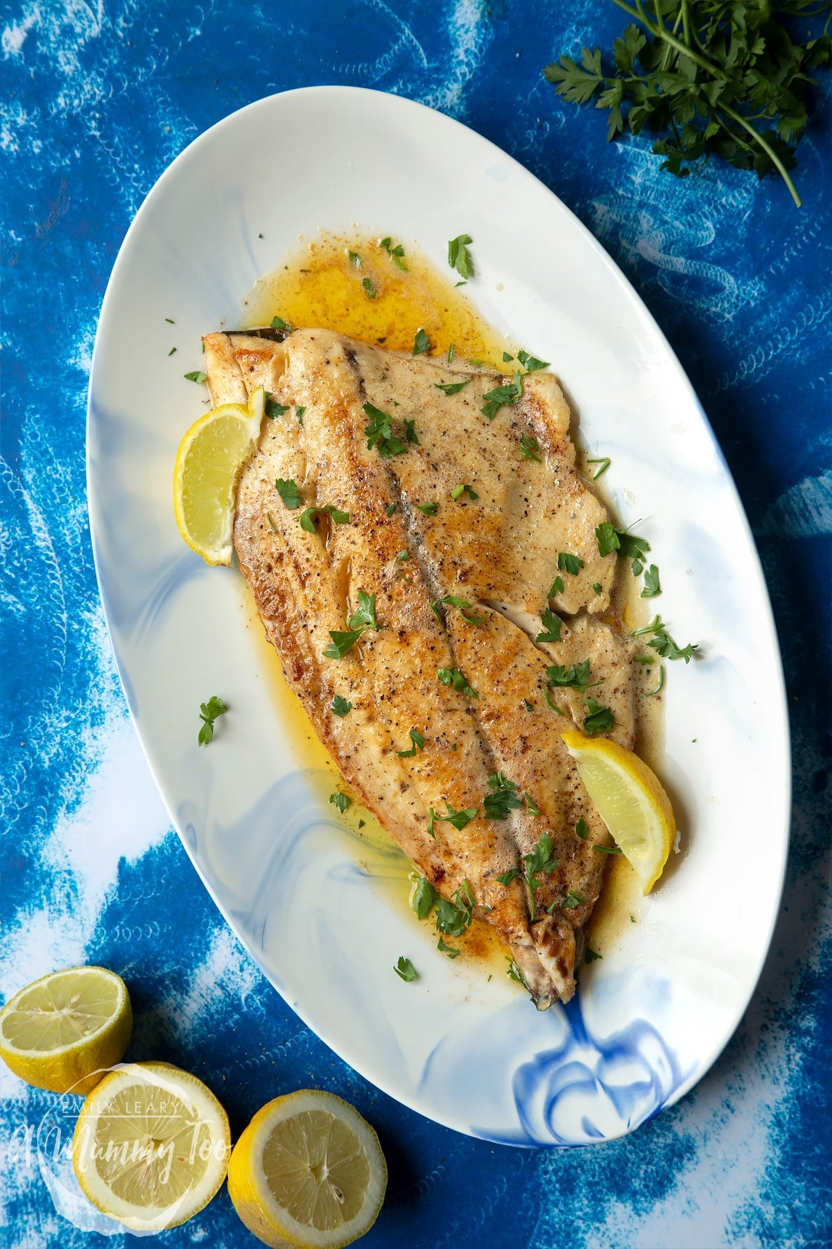 Pan-fried Yellowtail on an oval serving dish. The fish fillet is scattered with parsley and dotted with lemon wedges.