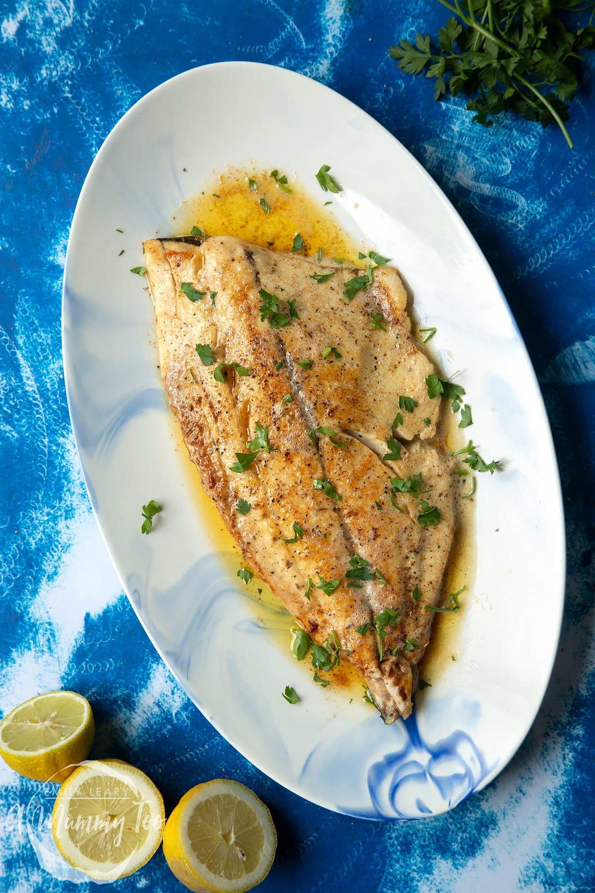 Pan-fried Yellowtail on an oval serving dish. The fish fillet is scattered with parsley.