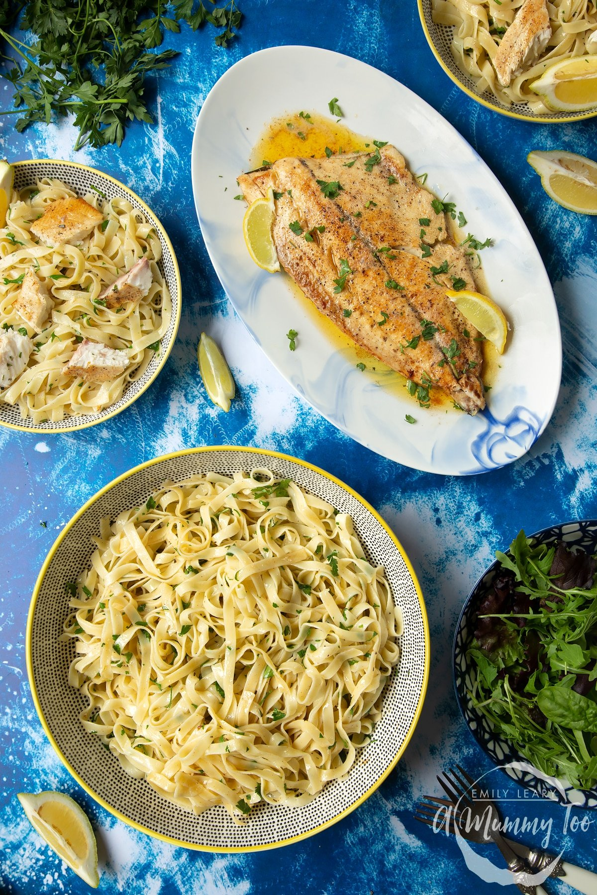 Pan-fried Yellowtail on a large oval serving dish. A large serving bowl of herby tagliatelle is also shown.