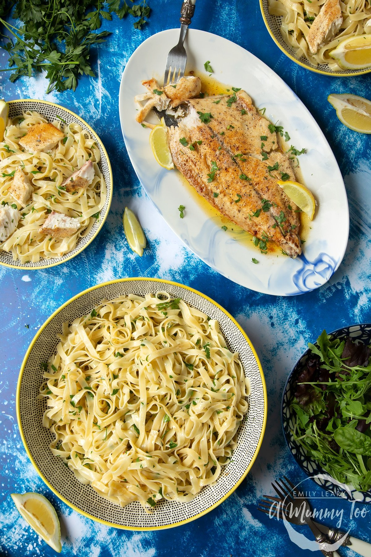 Pan-fried Yellowtail on a large oval serving dish. A fork delves into the buttery fish. A large serving bowl of herby tagliatelle is also shown.