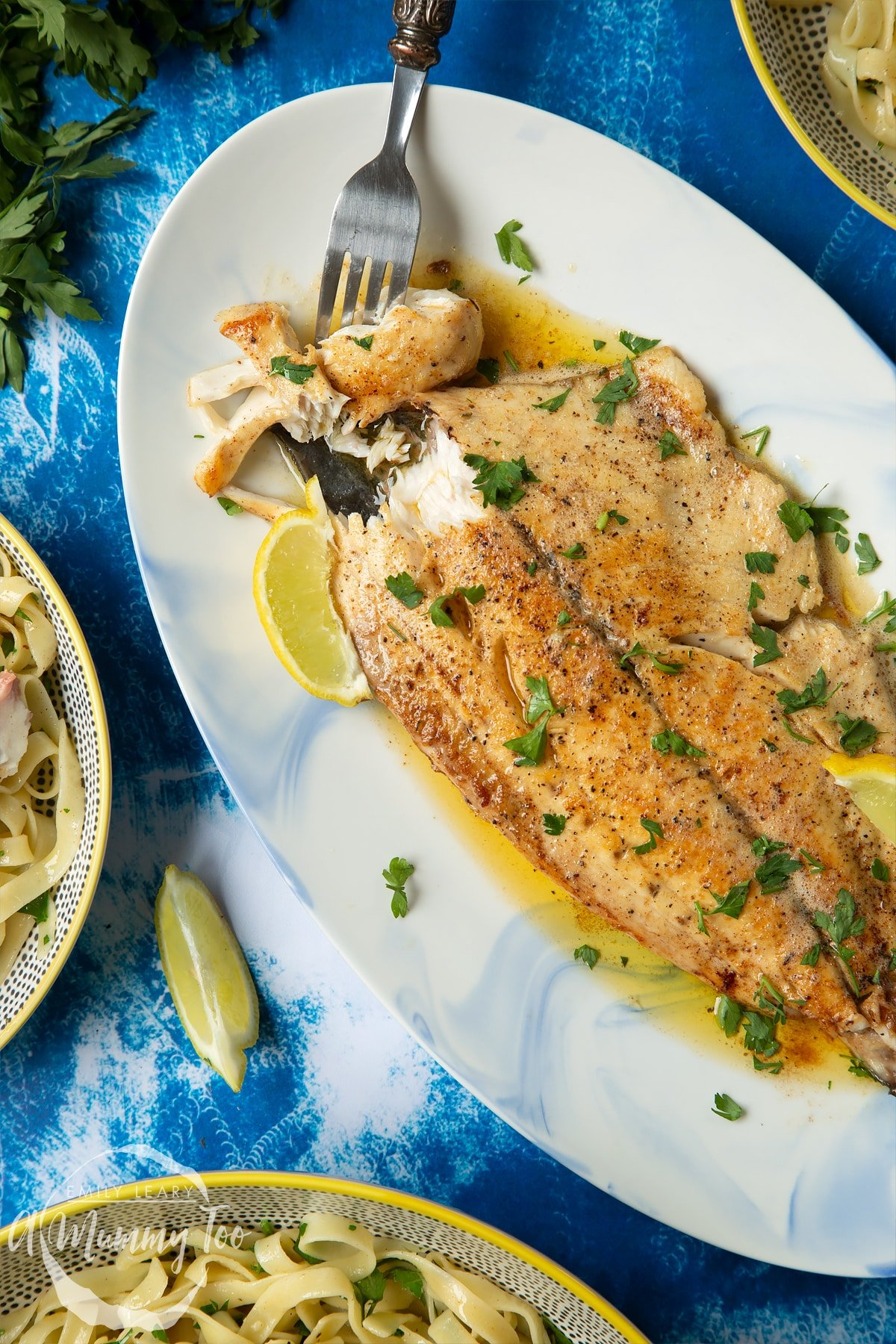 Pan-fried Yellowtail on a large oval serving dish. A fork delves into the buttery fish.