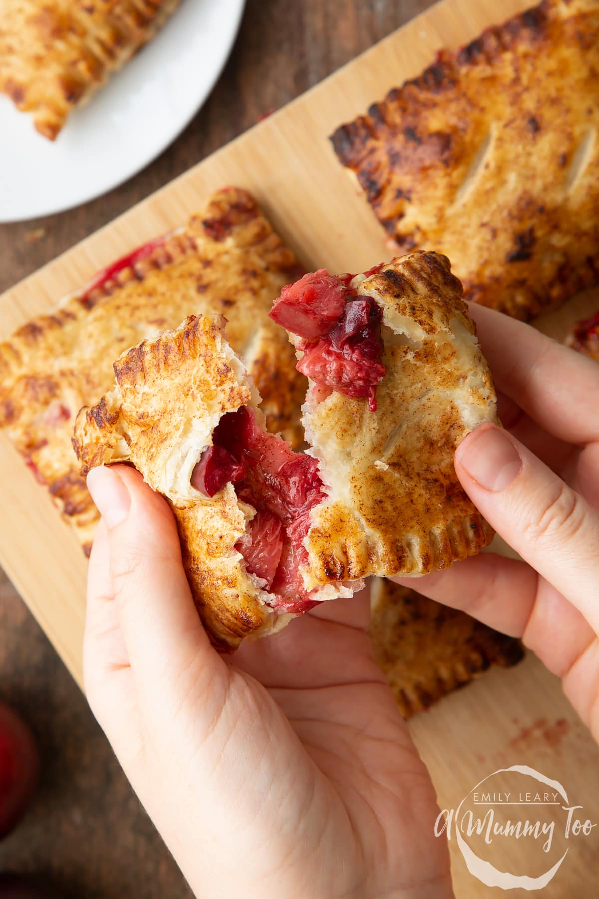 Two hands holding a plum pastry. It is broke open, showing the filling inside. More pastries are shown on a board in the background.