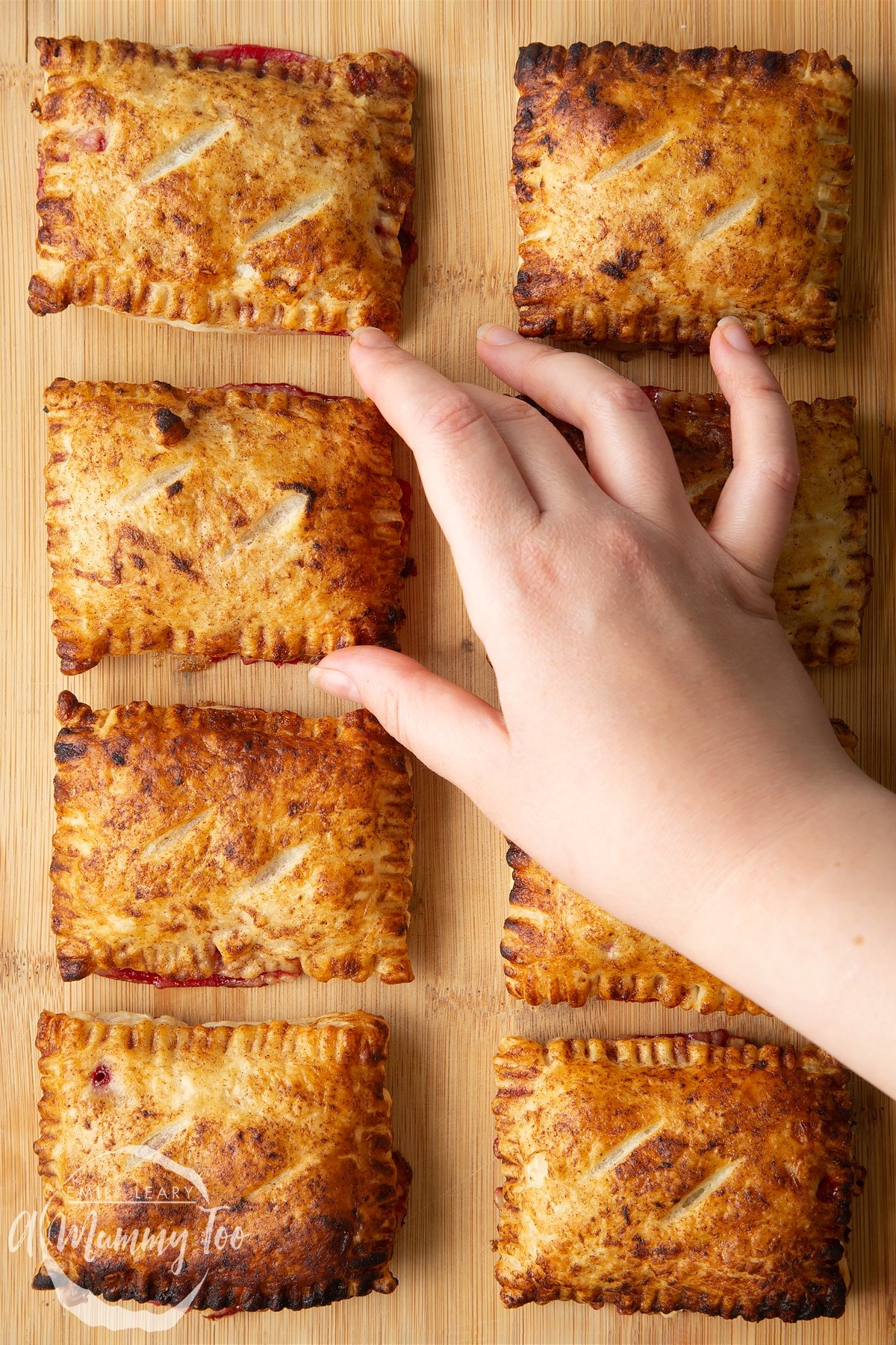 Eight plum pastries on a wooden board. A hand reaches to take one.
