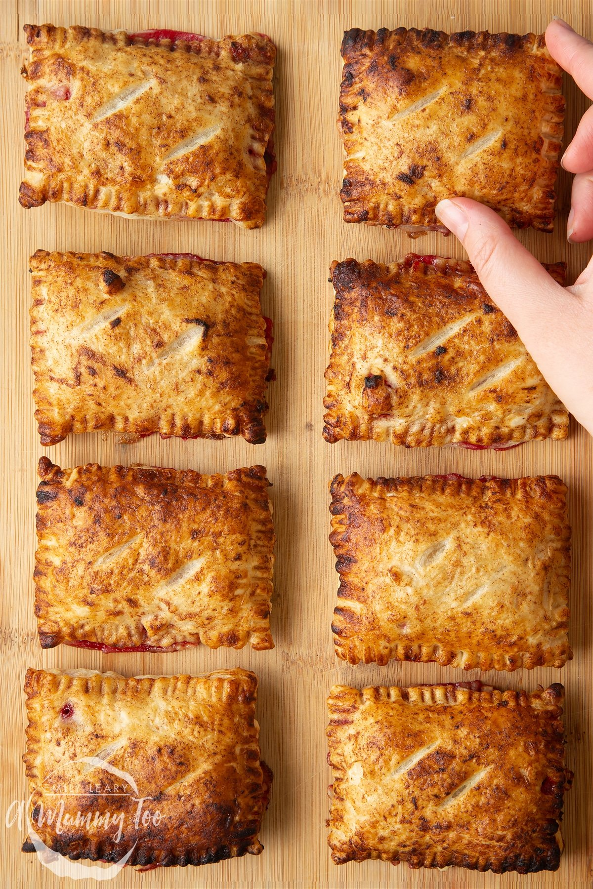 Eight plum pastries on a wooden board. A hand reaches to take the one in the top corner.