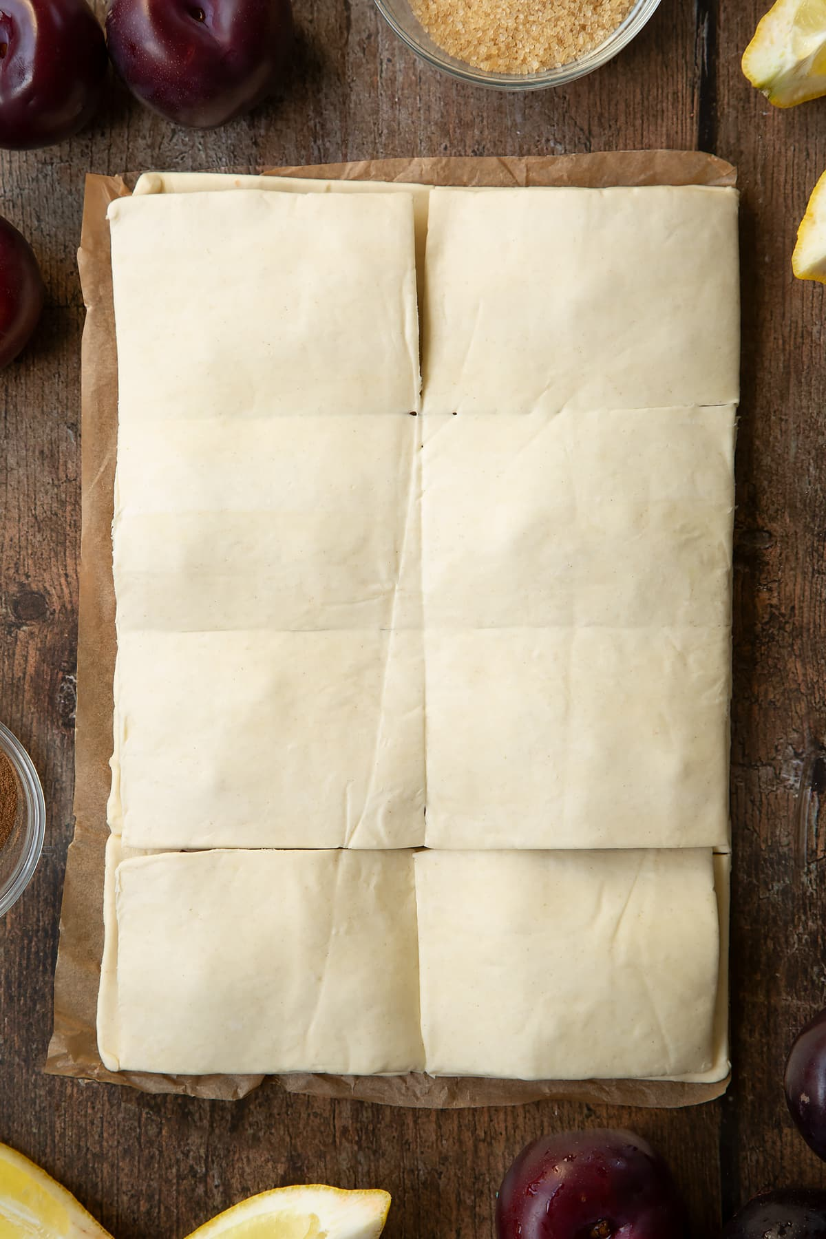 A puff pastry sheet topped with chopped plums and another sheet laying on top of it. Ingredients to make a plum pastry recipe surround the pastry.