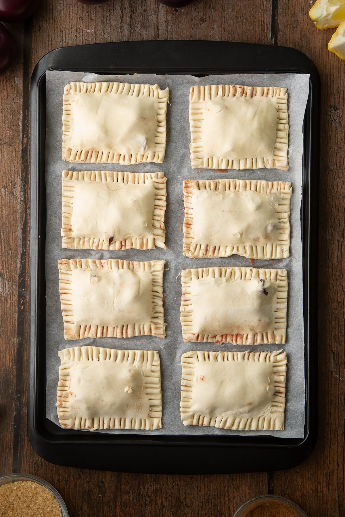 Puff pastry parcels on a baking paper lined tray. The edges are crimped with a fork and trimmed. Ingredients to make a plum pastry recipe surround the tray.