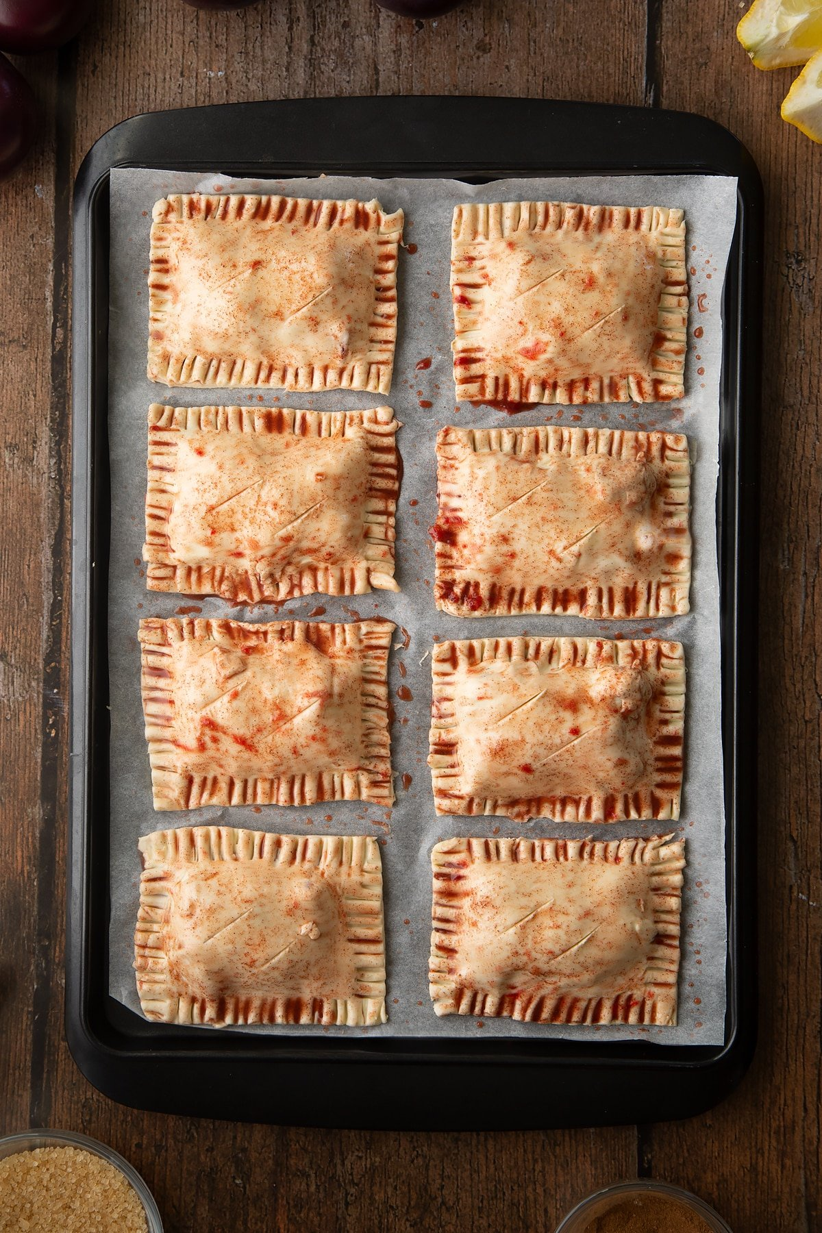 Puff pastry parcels on a baking paper lined tray. The parcels have been brush with plum juice. Slits have been cut across the top of each. Ingredients to make a plum pastry recipe surround the tray.