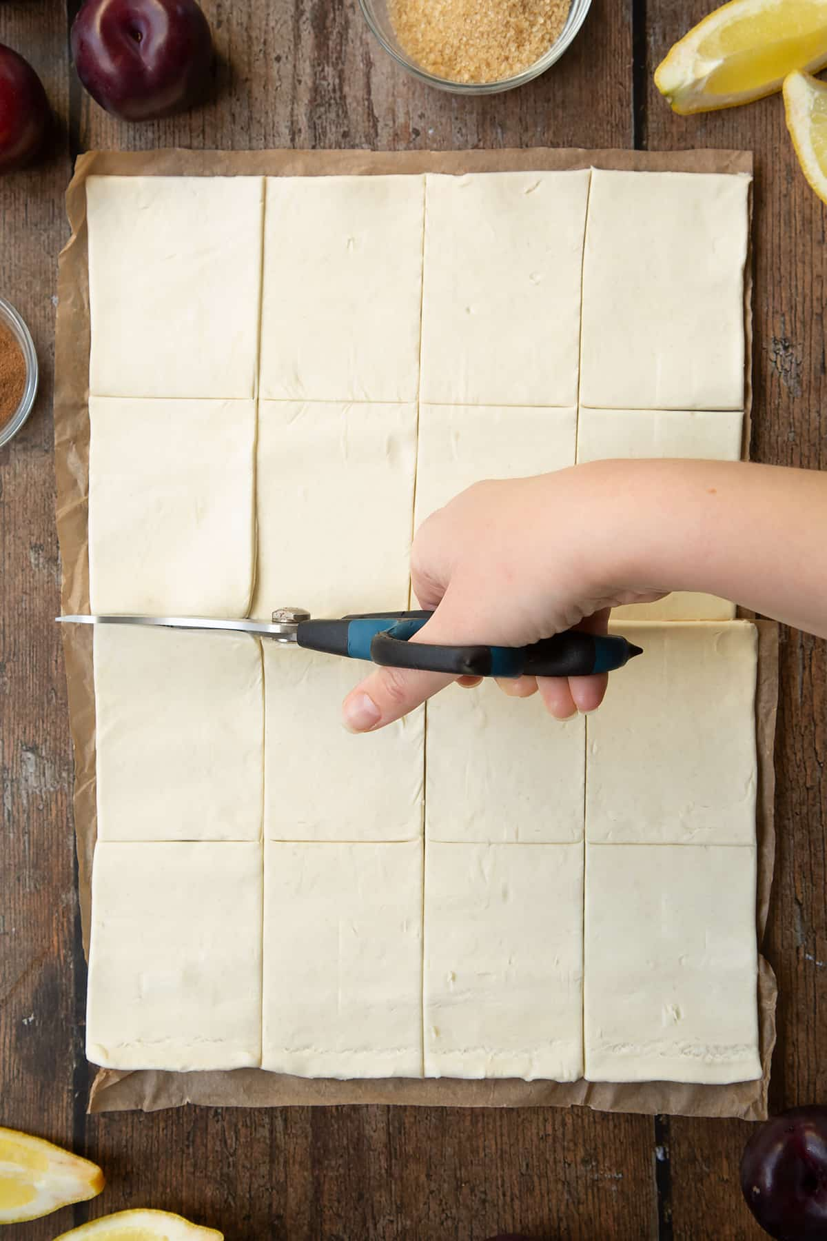 A puff pastry sheet cut into 16 pieces. Scissors are cutting the sheet in half. Ingredients to make a plum pastry recipe surround the pastry.