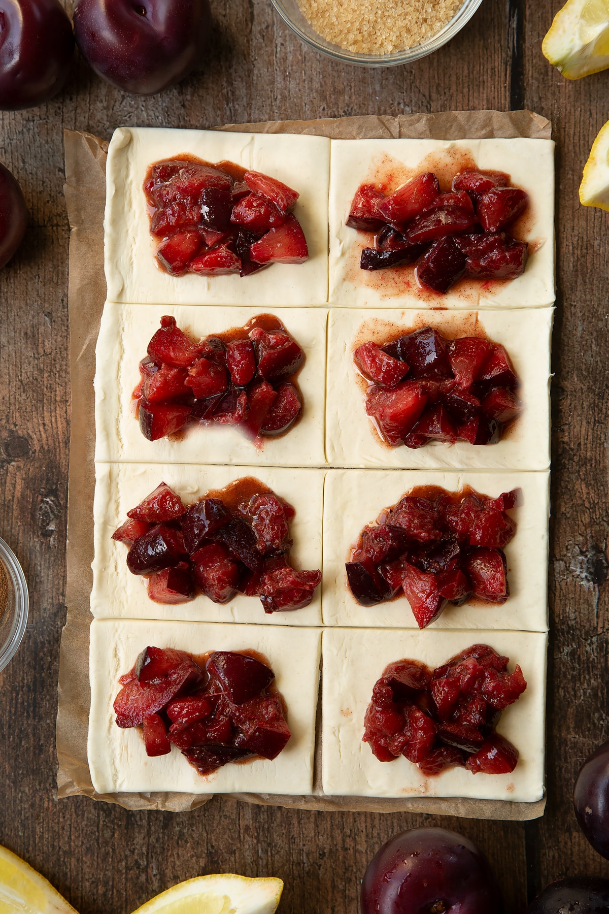 A puff pastry sheet cut into 8 pieces. Each piece is topped with chopped plums. Ingredients to make a plum pastry recipe surround the pastry.