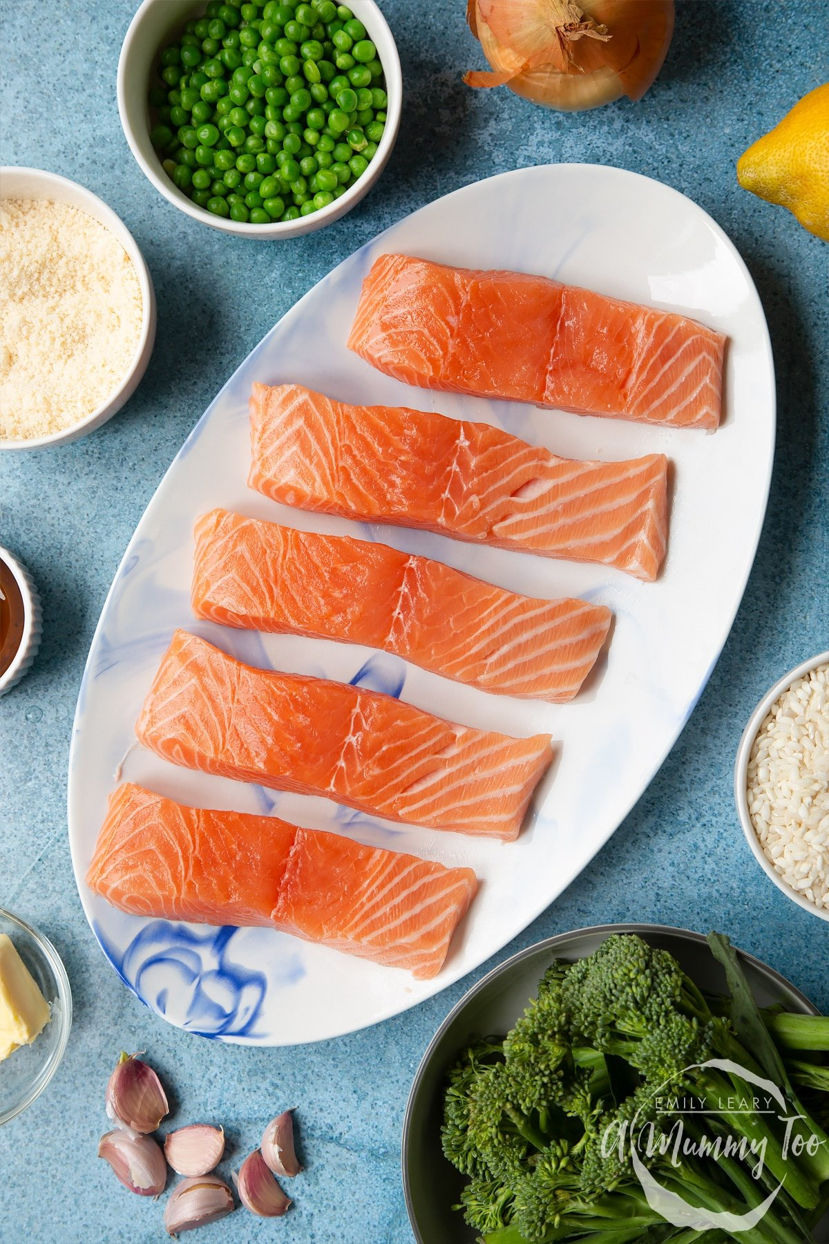 Fresh Scottish salmon fillets on a white, oval plate. Ingredients to make salmon risotto surround the plate.