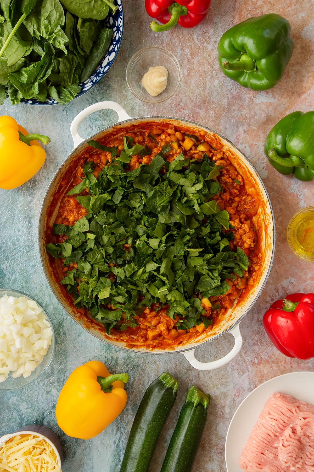 Vegetables, turkey mince and baked beans simmered in a spicy tomato sauce in a large shallow pan with spinach on top. Ingredients to make baked bean stuffed peppers surround the pan.
