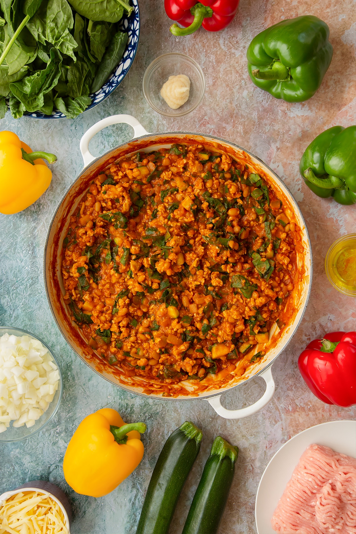 Vegetables, turkey mince, baked beans and wilted spinach in a spicy tomato sauce in a large shallow pan. Ingredients to make baked bean stuffed peppers surround the pan.