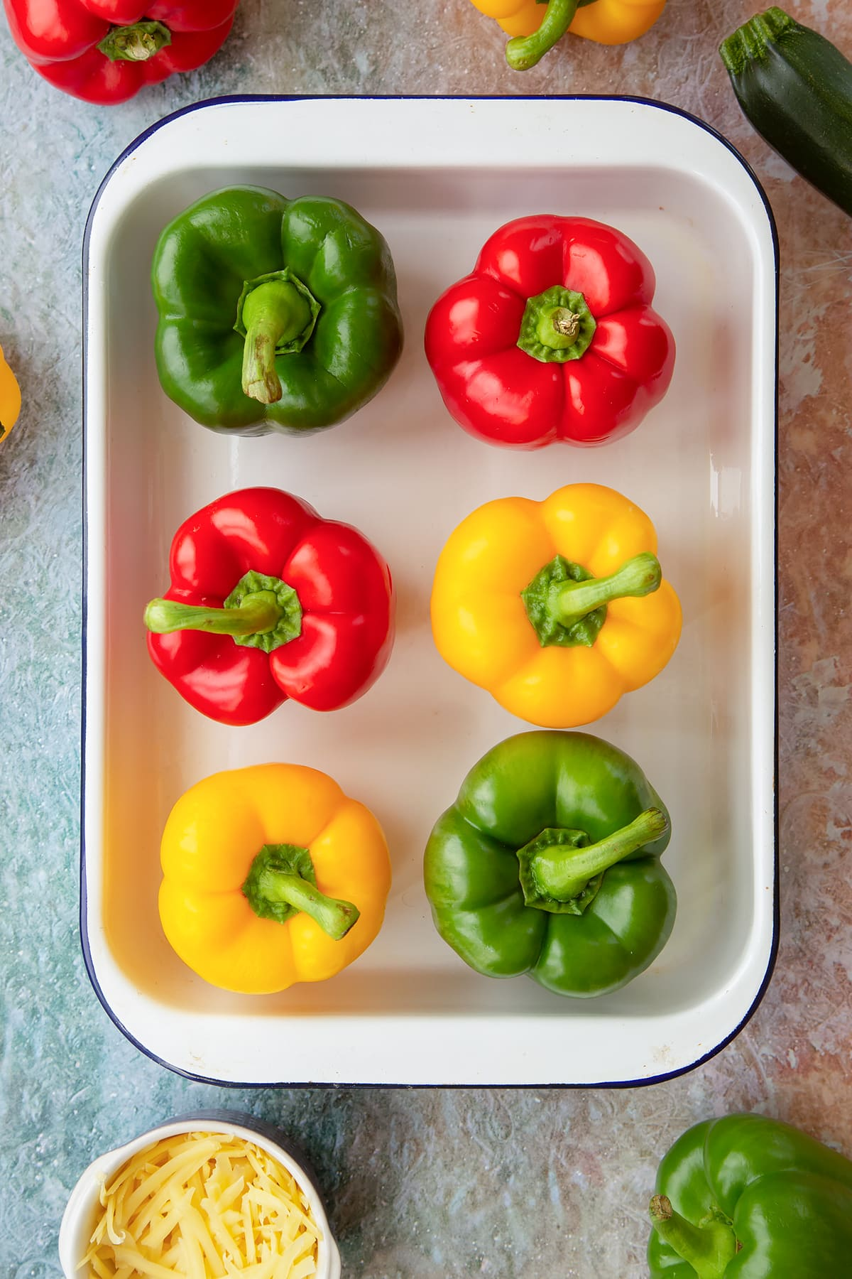 Six red, green and yellow peppers in a white roasting tray. Ingredients to make baked bean stuffed peppers surround the tray.