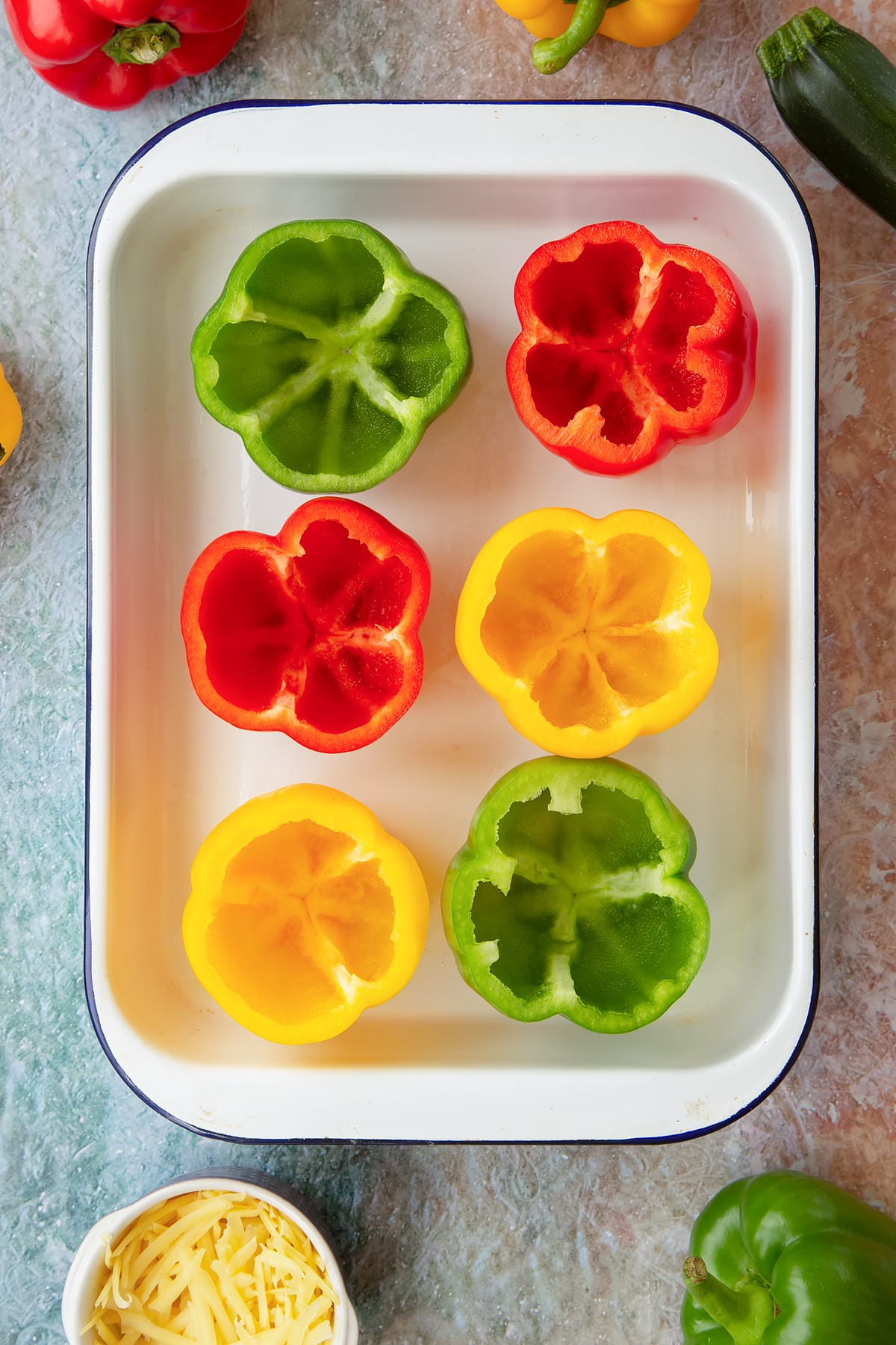 Six red, green and yellow peppers in a white roasting tray with their tops cut off and seeds removed. Ingredients to make baked bean stuffed peppers surround the tray.