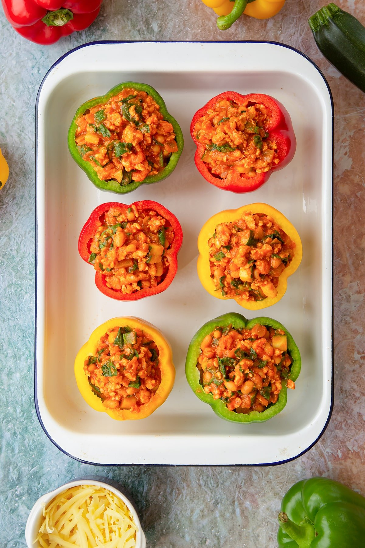 Six red, green and yellow peppers in a white roasting tray. The peppers are filled with the bean and turkey mix. Ingredients to make baked bean stuffed peppers surround the tray.
