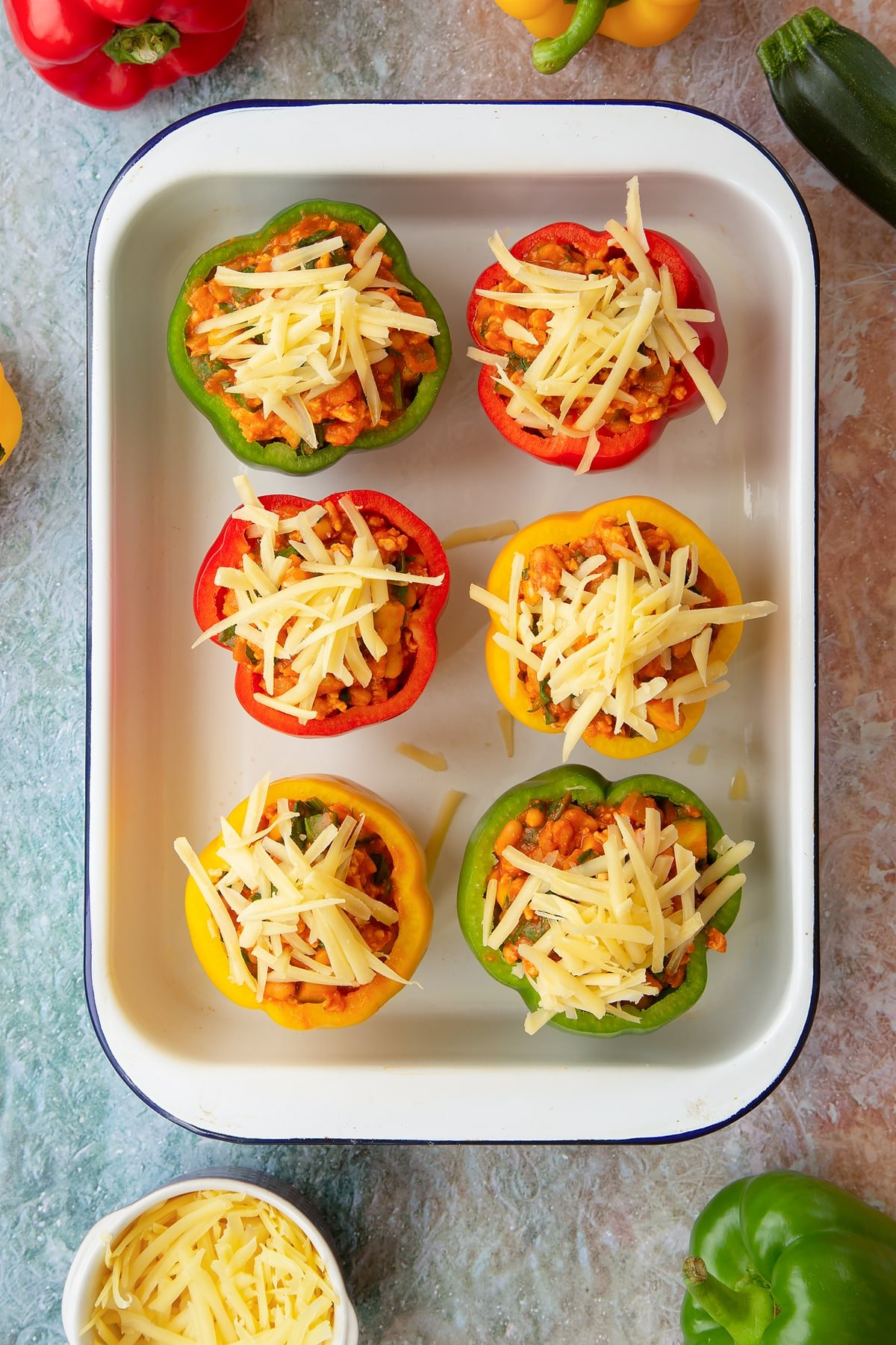 Six red, green and yellow peppers in a white roasting tray. The peppers are filled with the bean and turkey mix and topped with grated cheese. Ingredients to make baked bean stuffed peppers surround the tray.