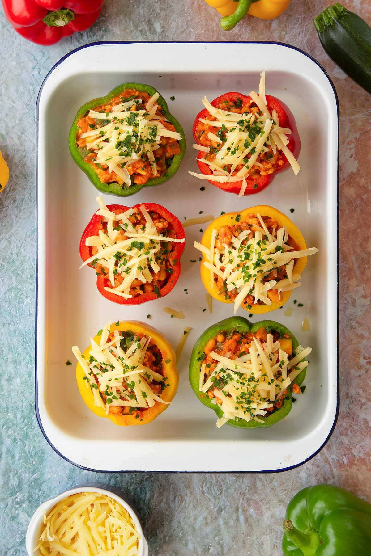 Freshly made baked bean stuffed peppers in a white roasting tray.