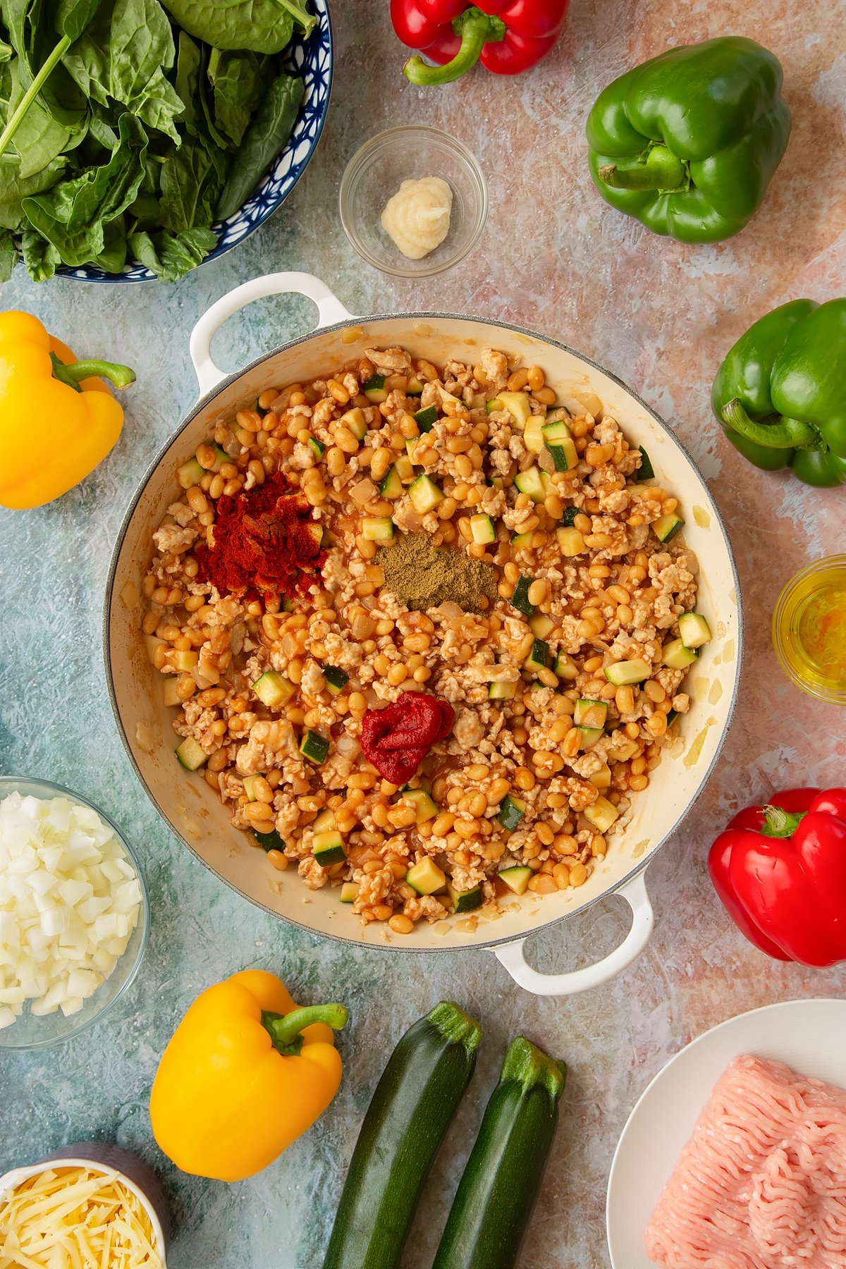Onions, garlic, turkey mince, courgette, baked beans and turkey mince in a large shallow pan, with tomato puree, cumin and smoked paprika on top. Ingredients to make baked bean stuffed peppers surround the pan.