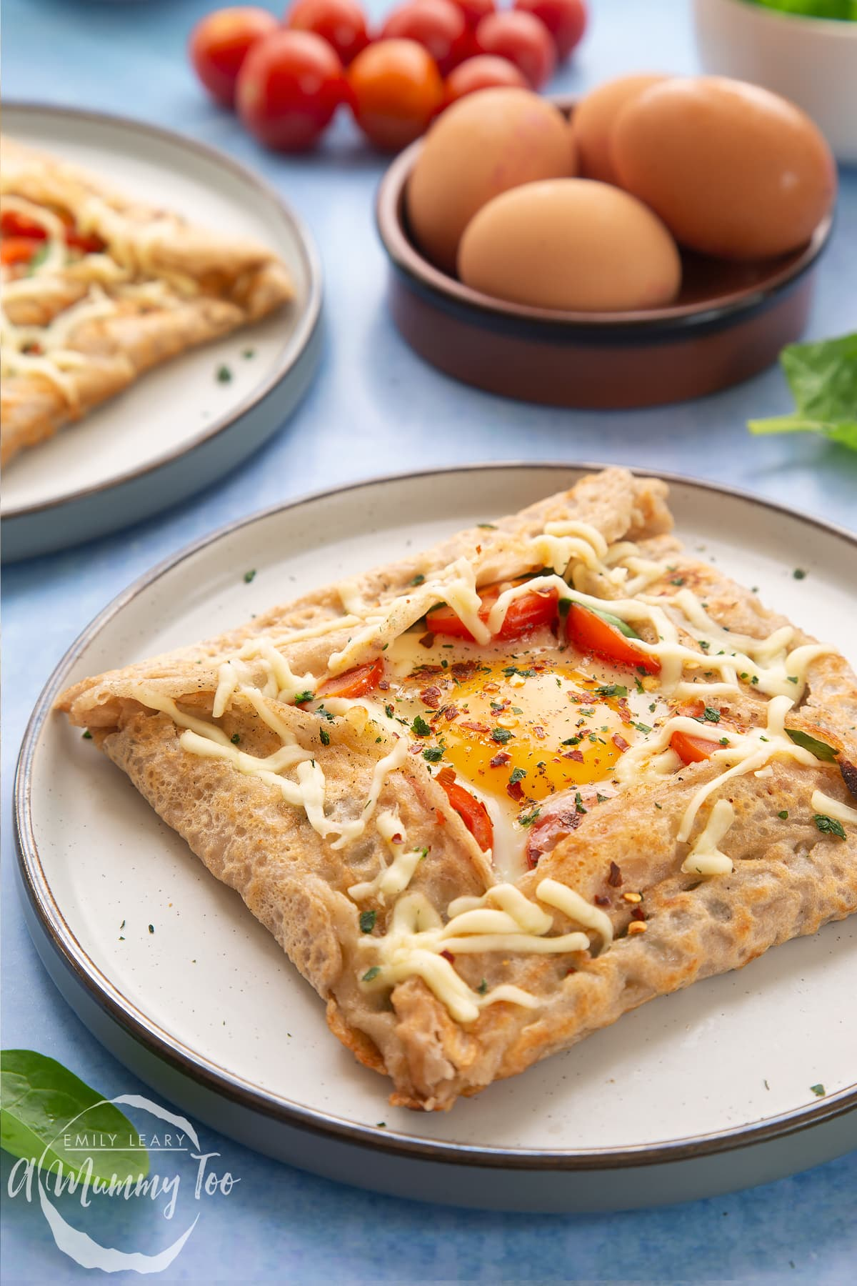 A buckwheat galette on plate with ingredients and another plate behind it. The galette is filled with spinach, tomatoes, cheese and a lightly cooked egg.