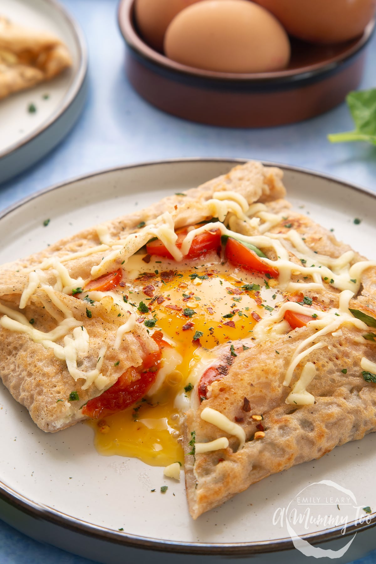A buckwheat galette on plate with ingredients behind it. The galette is filled with spinach, tomatoes, cheese and a lightly cooked egg.