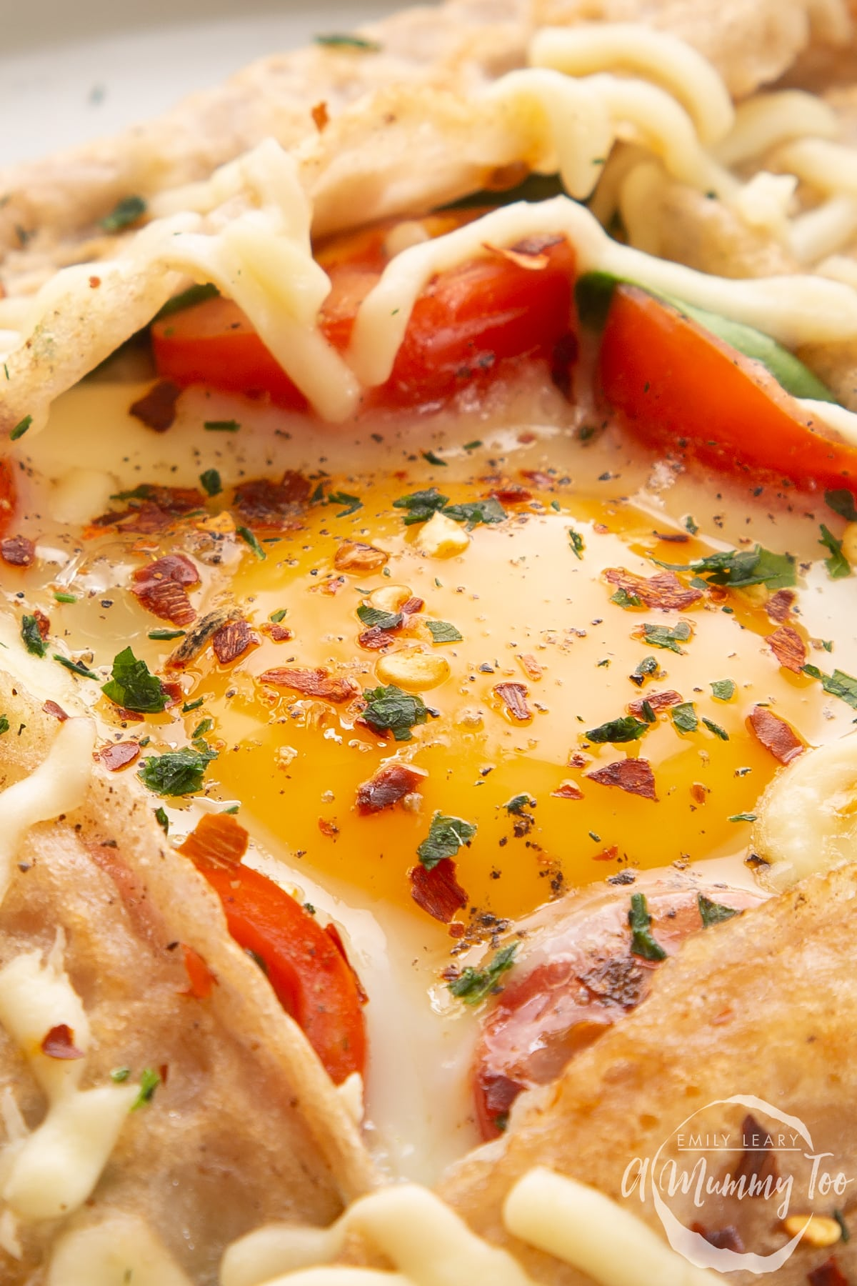 Close up on the yolk in a buckwheat galette filled with spinach, tomatoes, cheese and a lightly cooked egg.