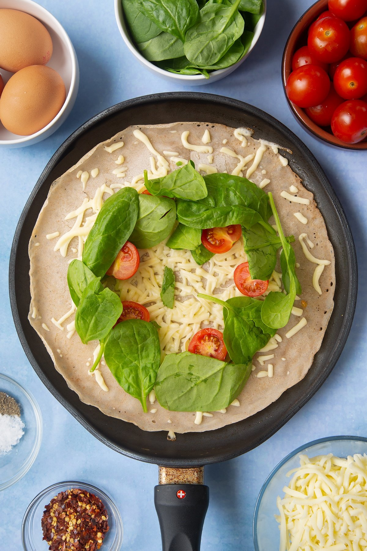 Buckwheat crepe topped with grated cheese, cherry tomatoes and spinach in a crepe pan. Ingredients to make buckwheat galettes surround the pan.